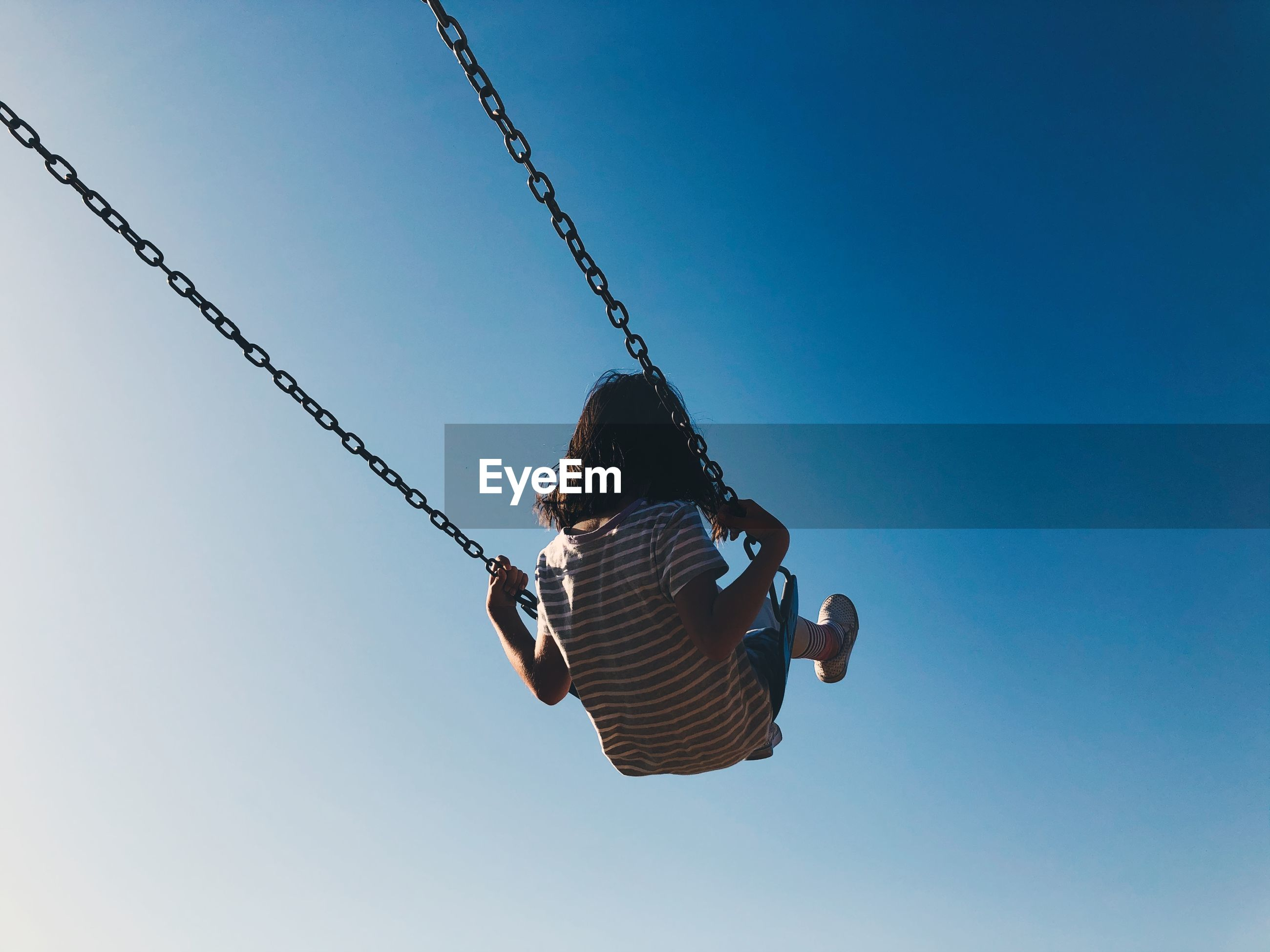 Rear view of girl on swing at playground