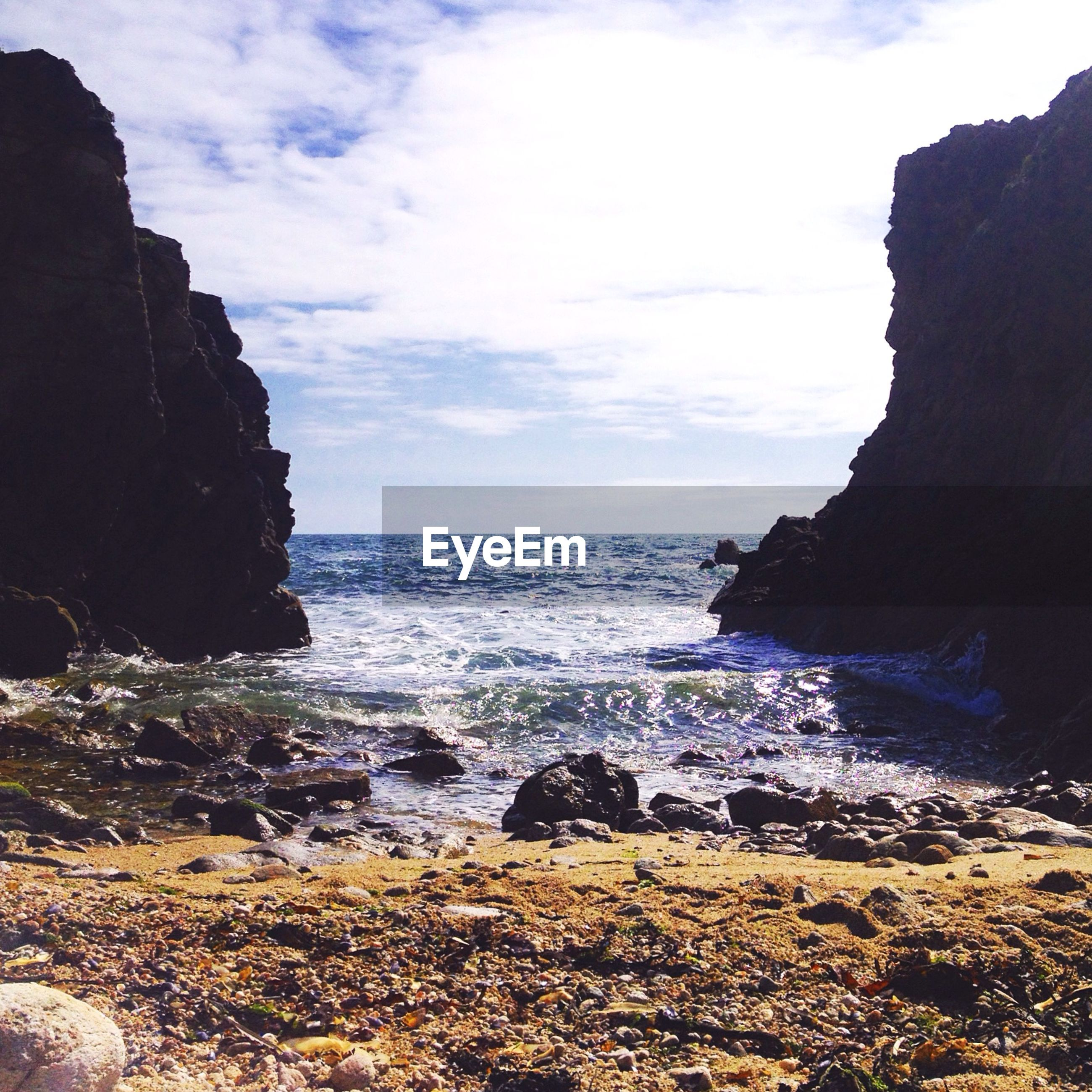 Scenic view of sea amidst rock formations against cloudy sky