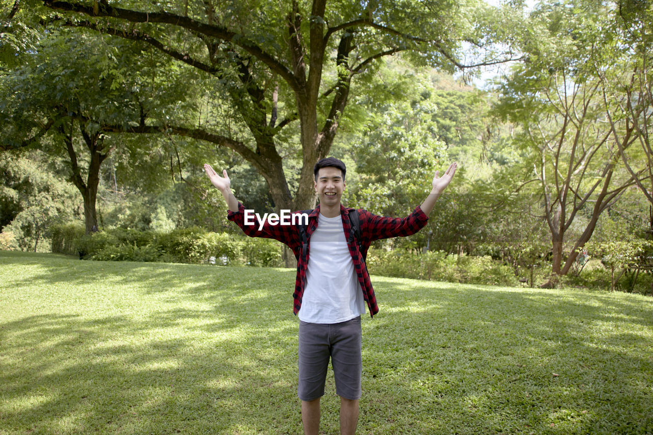 Portrait of young man gesturing while standing at park