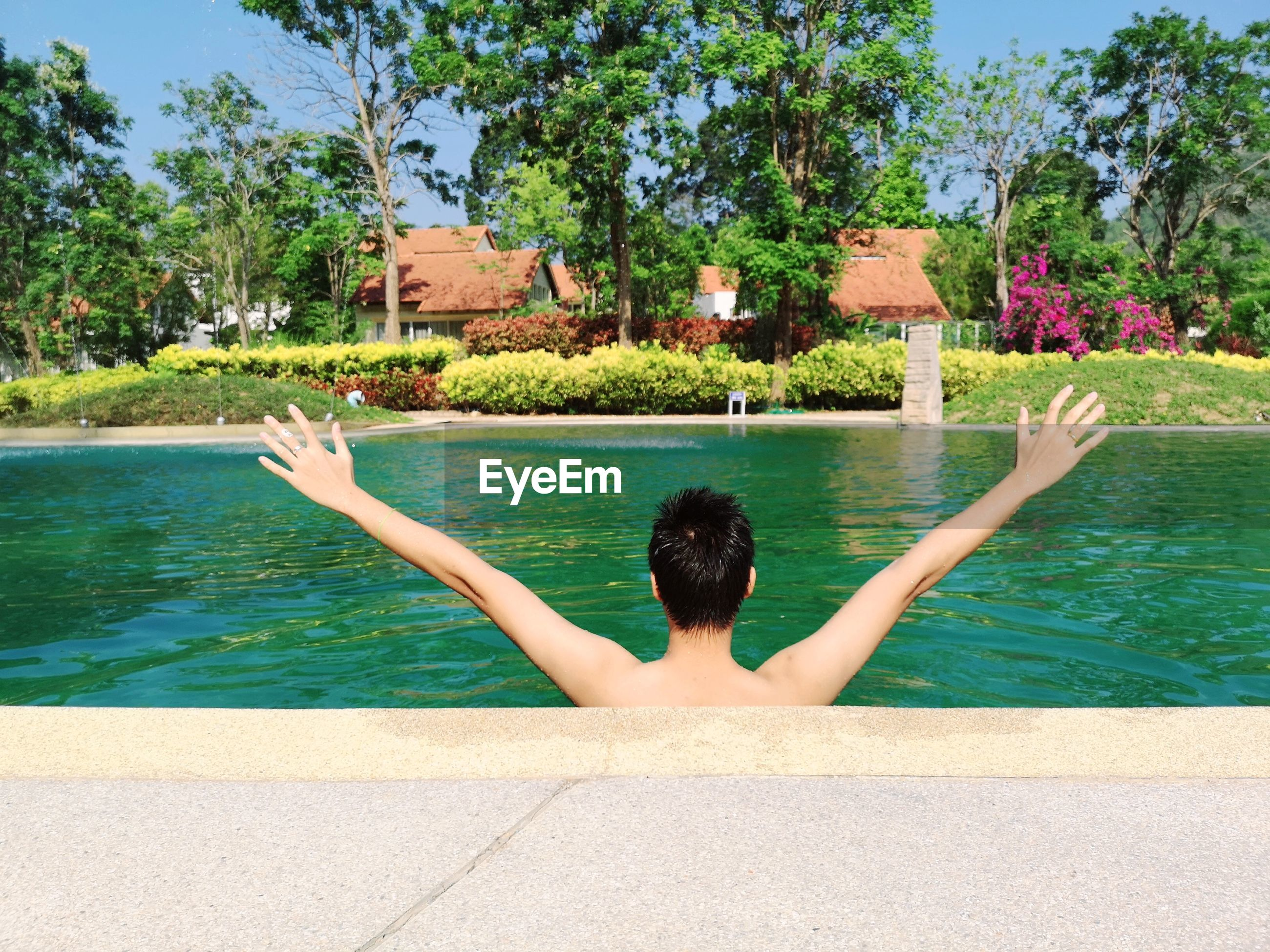 Rear view of man with arms outstretched in swimming pool
