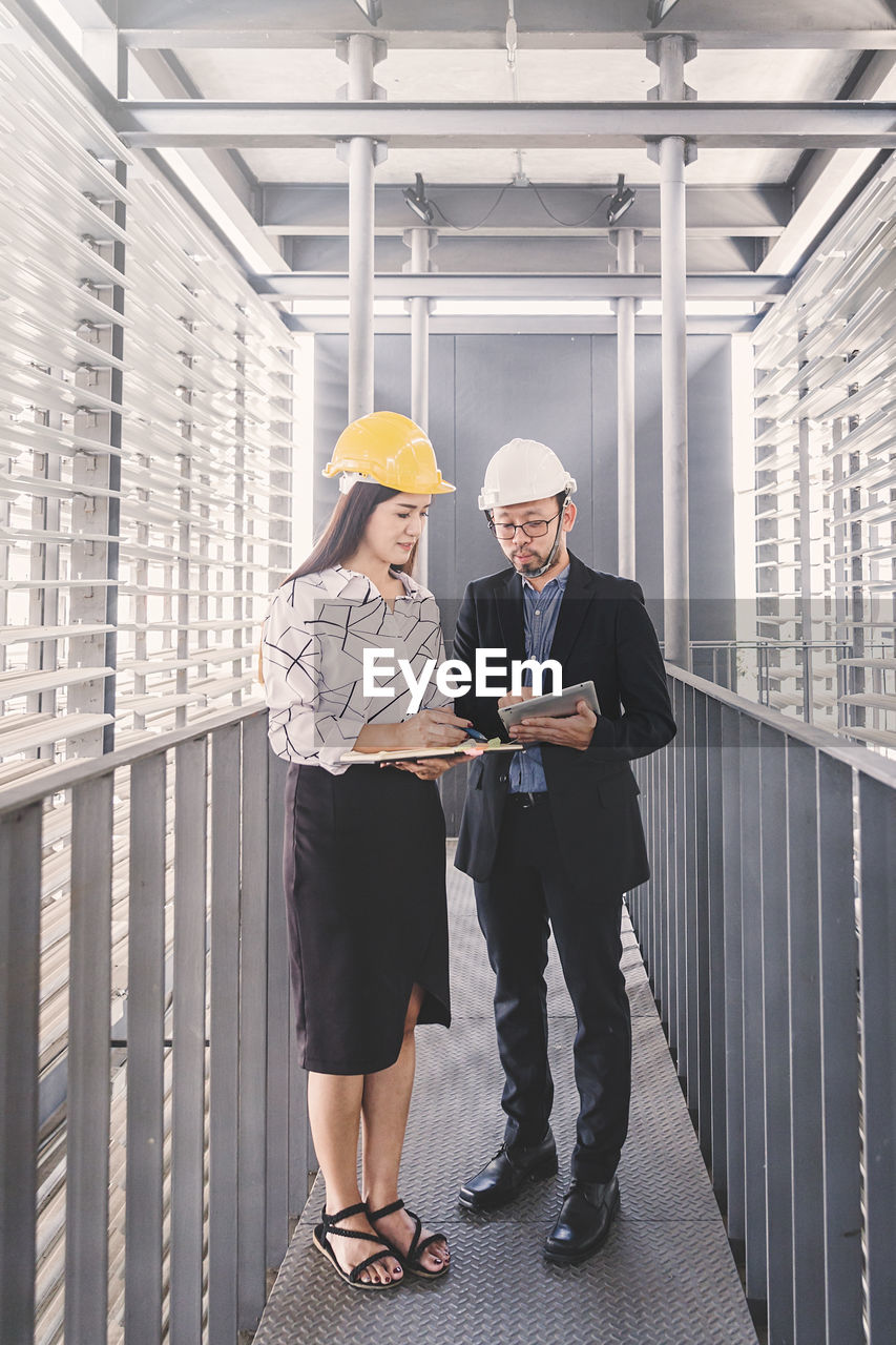 men, architecture, two people, communication, standing, real people, well-dressed, males, adult, full length, occupation, young adult, built structure, office, indoors, business, wireless technology, front view, cooperation, mature men, mature adult, teamwork