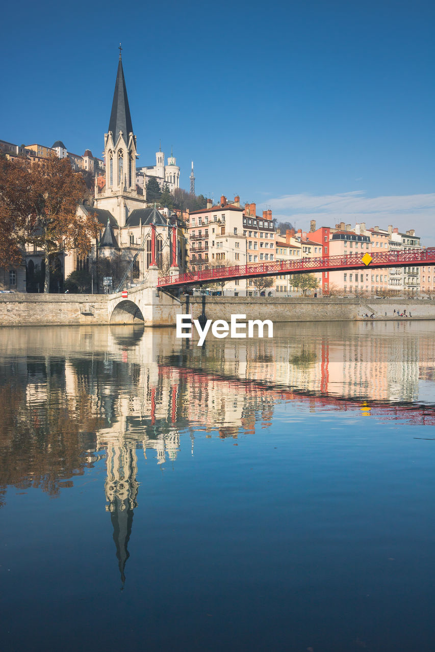 Reflection of buildings in river against clear blue sky in lyon