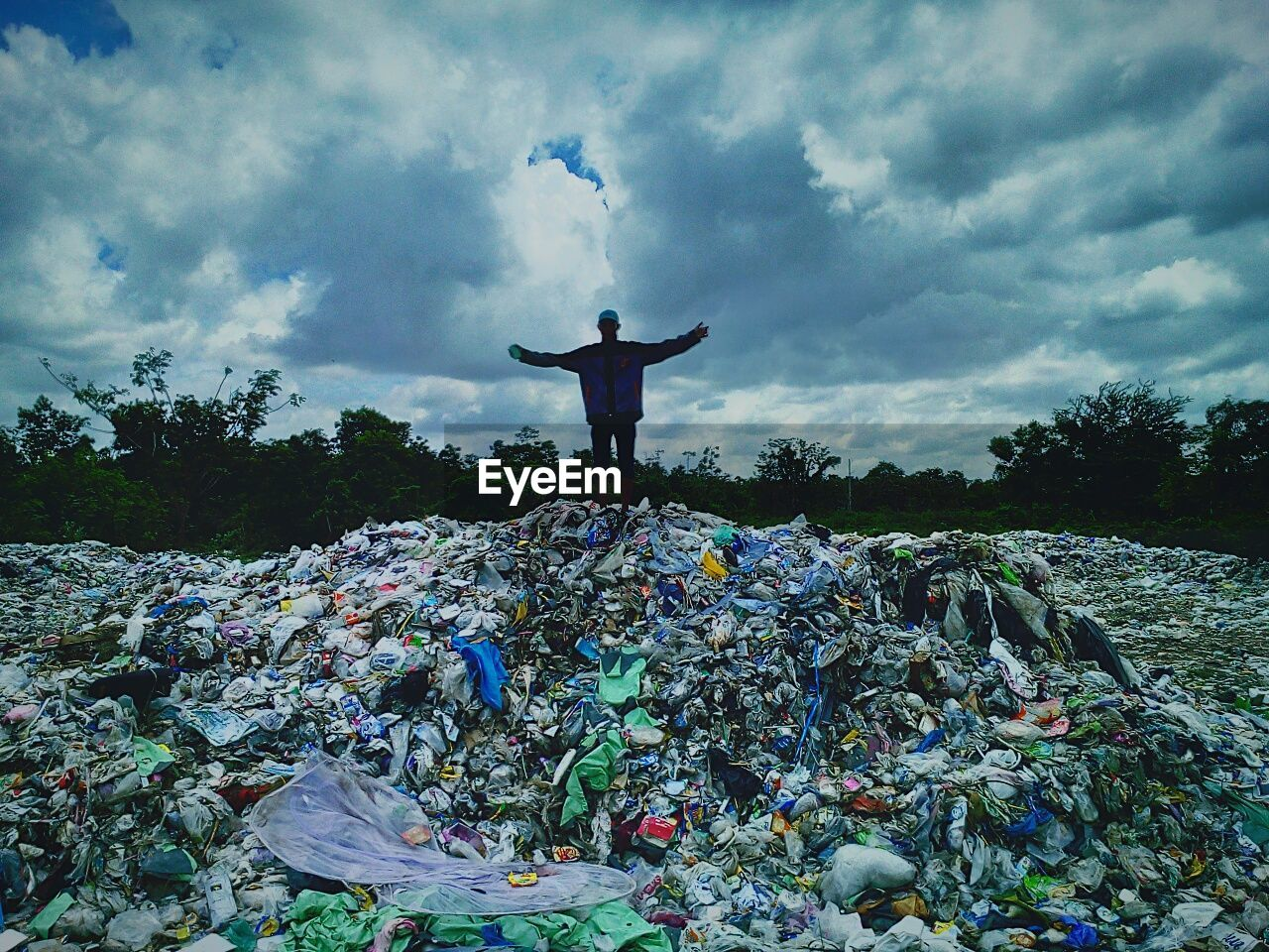 cloud - sky, sky, one person, arms raised, arms outstretched, garbage, men, standing, day, full length, real people, one man only, outdoors, nature, energetic, young adult, only men, adult, people