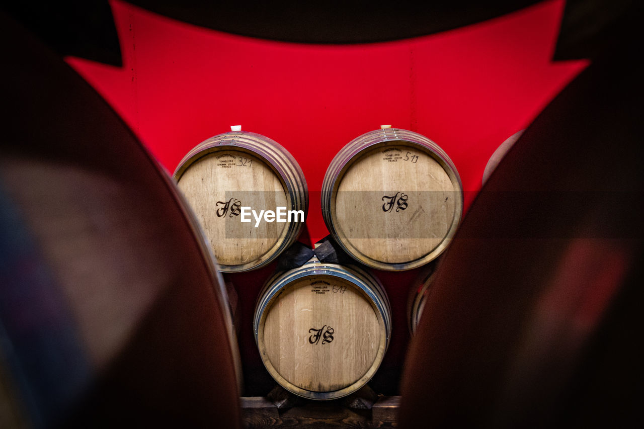 red, indoors, close-up, no people, selective focus, drink, refreshment, high angle view, food and drink, text, alcohol, day, barrel, still life, communication, side by side, focus on foreground, number, music, wine, winemaking