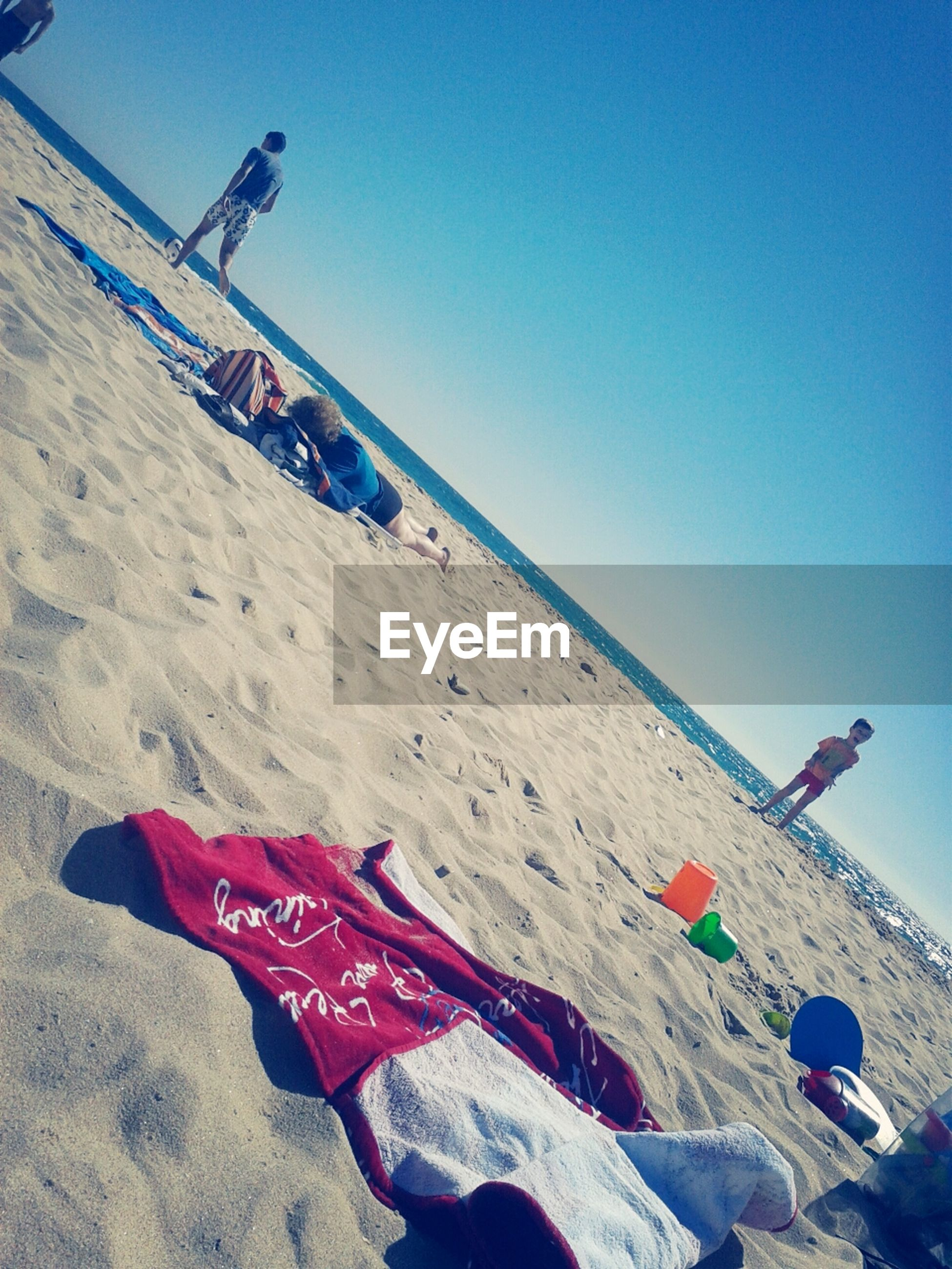 beach, sand, blue, clear sky, sea, flag, shore, copy space, sunlight, day, horizon over water, sky, tranquility, incidental people, nature, outdoors, vacations, summer, beach umbrella, identity