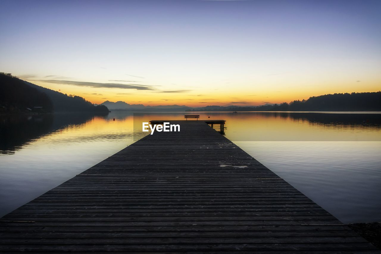 SCENIC VIEW OF PIER OVER LAKE AGAINST SKY DURING SUNSET