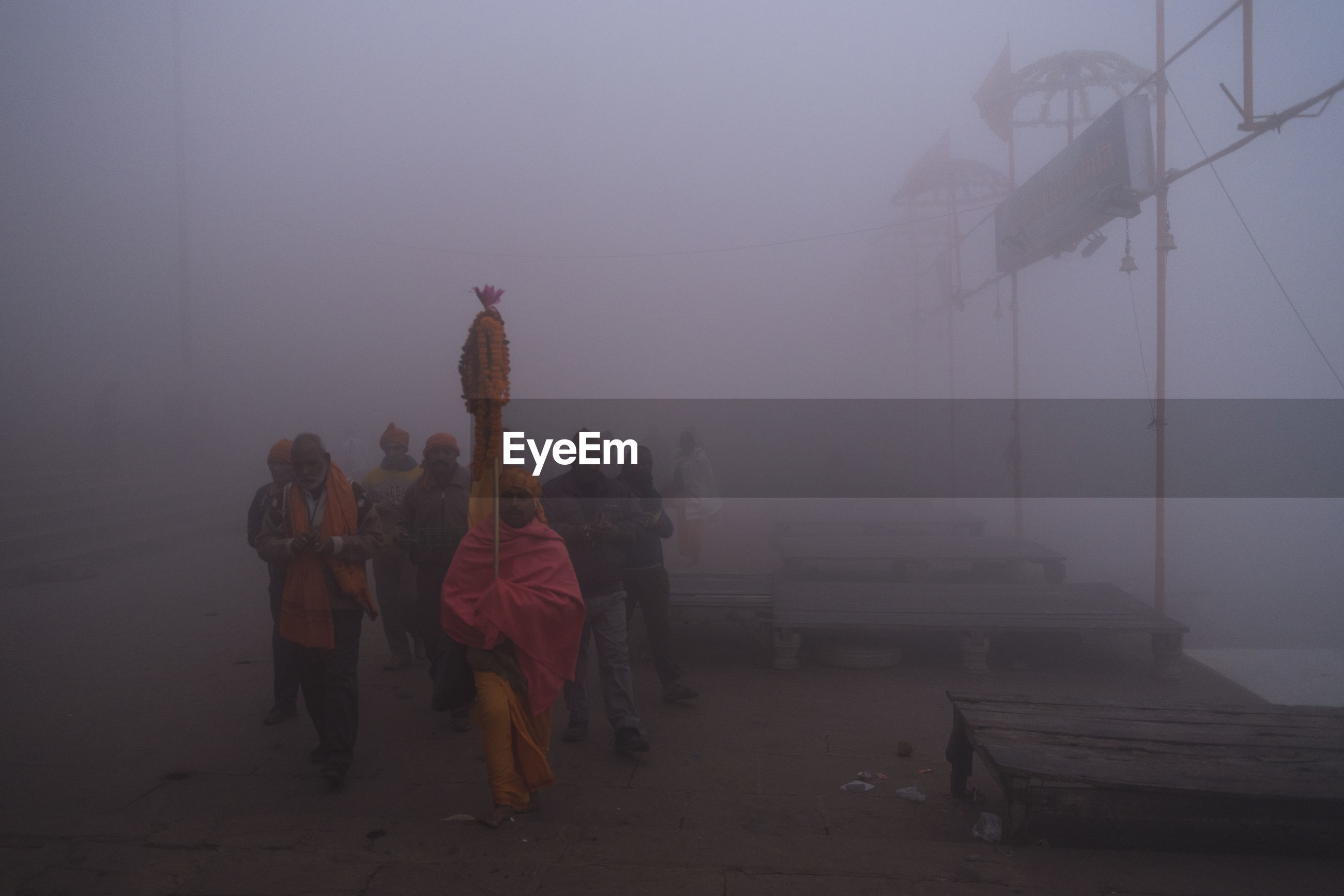 PEOPLE ON TEMPLE AGAINST SKY DURING FOGGY WEATHER