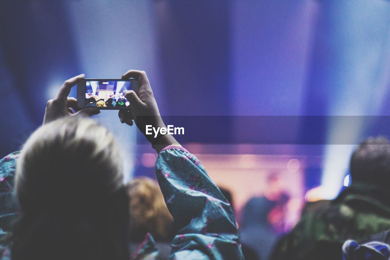 Rear View Of Woman Photographing Through Smart Phone At Concert