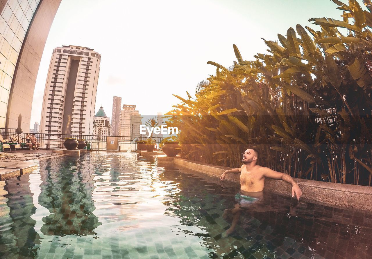 Shirtless man relaxing in swimming pool against sky