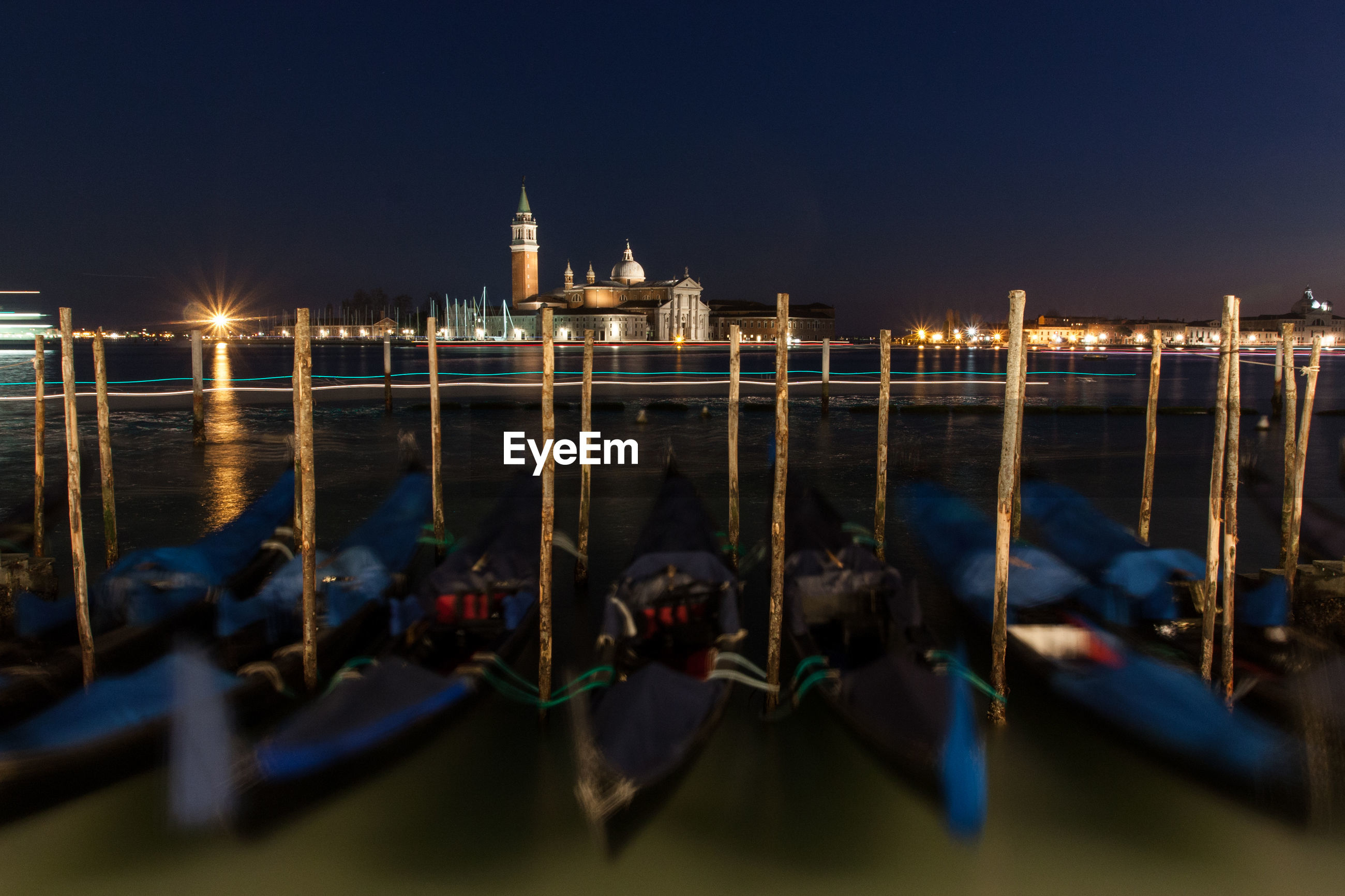Blurred motion of gondolas moored on grand canal against st marks square at night