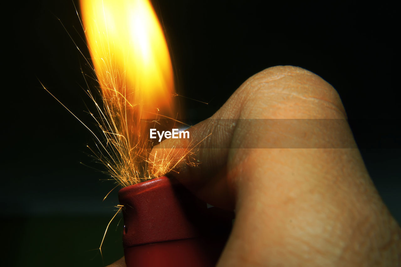 Close-up of hand holding cigarette lighter with flame and sparks against black background