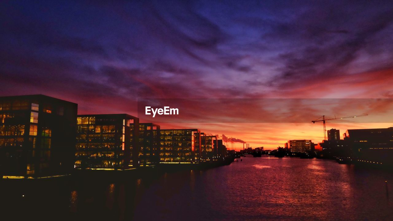 building exterior, architecture, sky, city, built structure, cloud - sky, sunset, water, building, nature, no people, waterfront, illuminated, orange color, cityscape, dusk, reflection, river, outdoors, office building exterior, skyscraper, romantic sky