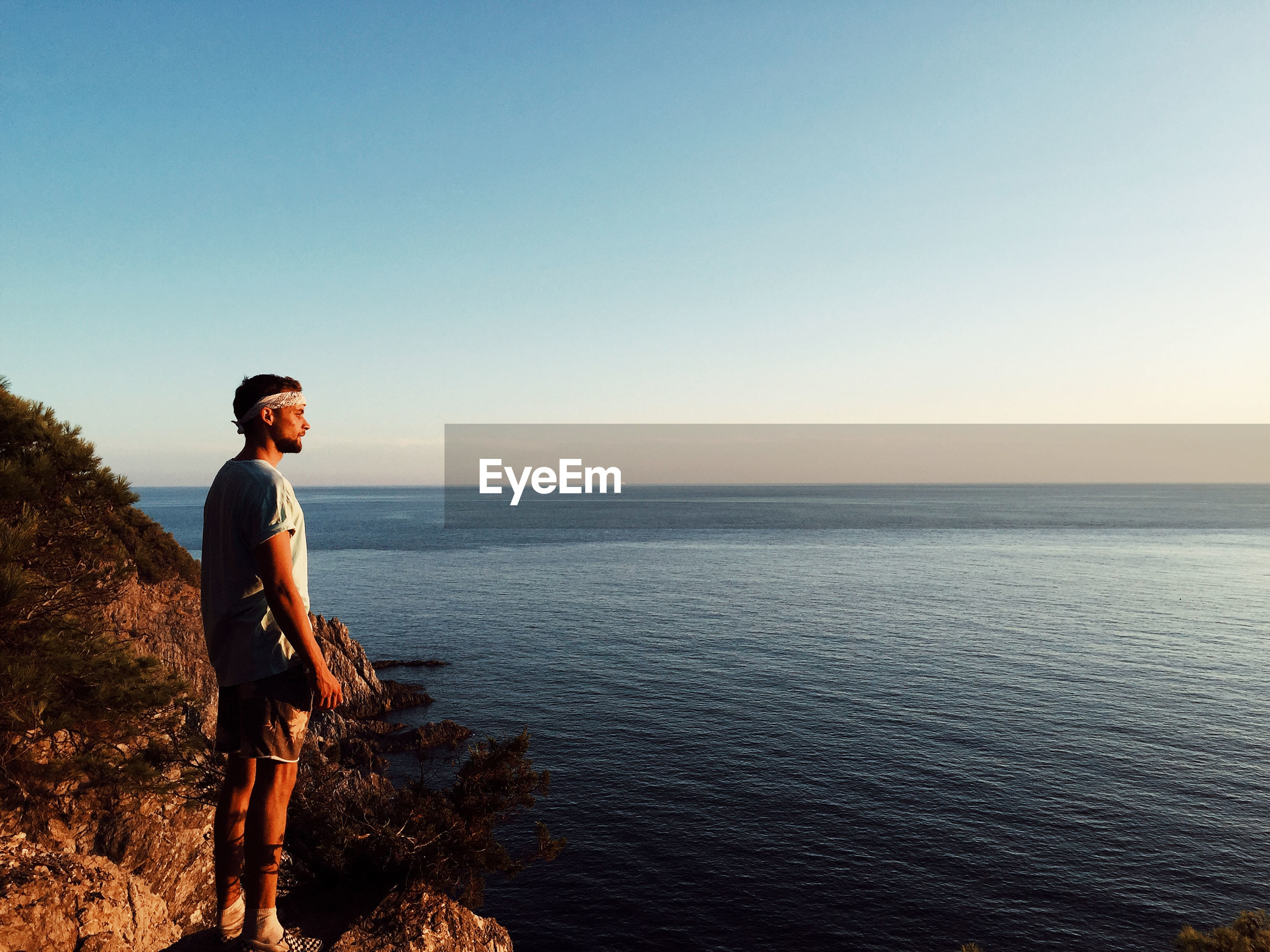 MAN STANDING ON SEA AGAINST CLEAR SKY