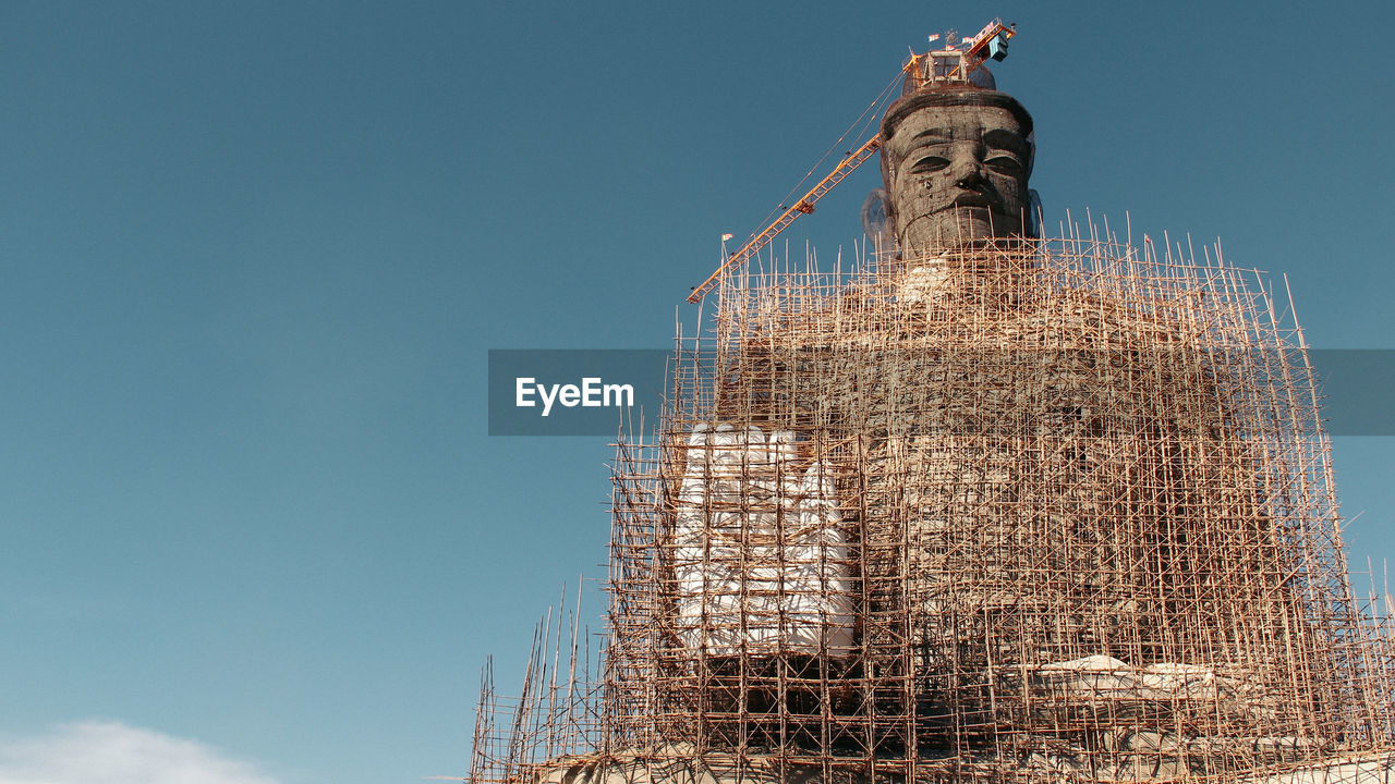 Low angle view of large buddha statue during construction