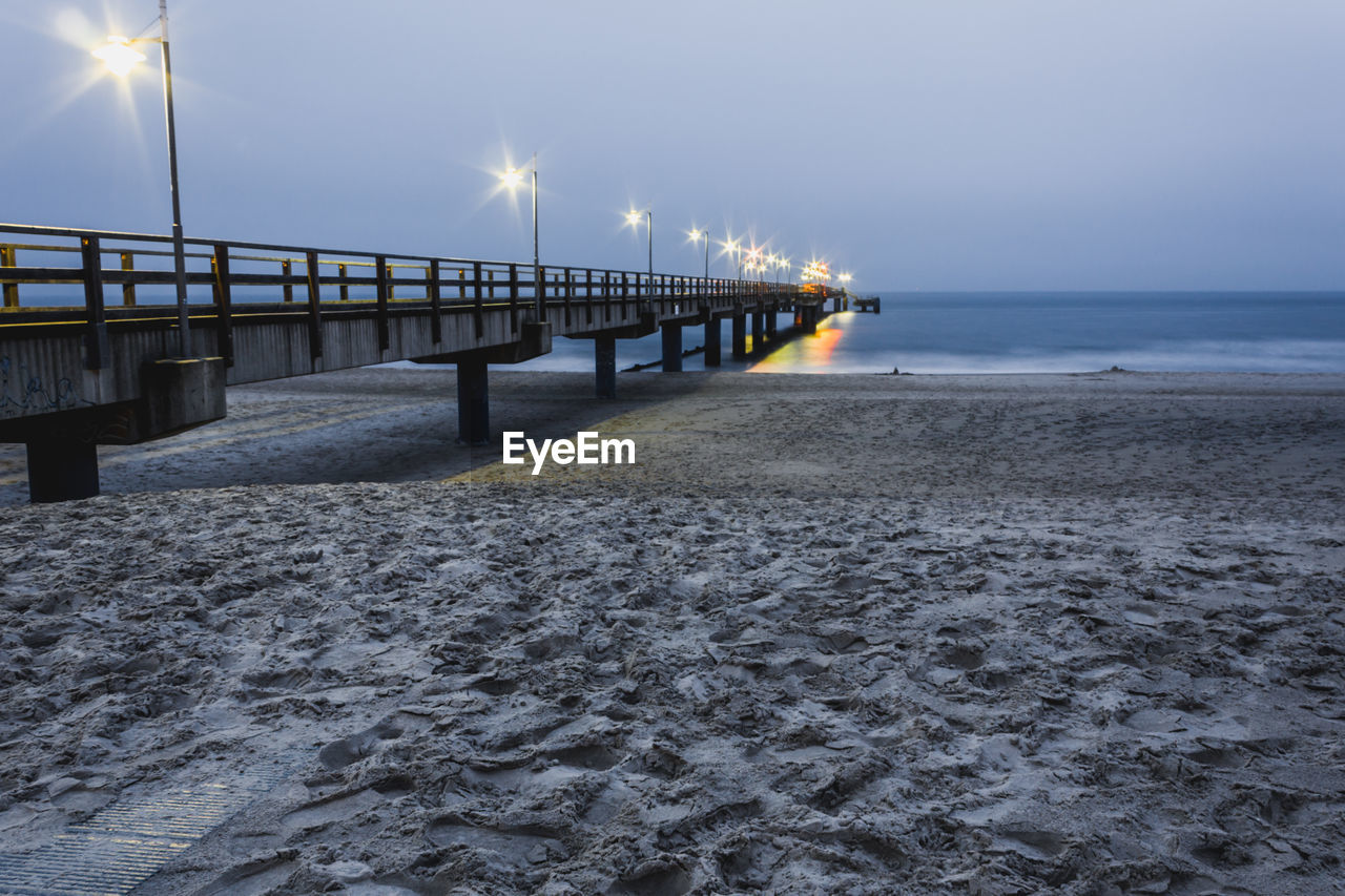 water, sea, sky, beach, horizon over water, built structure, land, architecture, scenics - nature, horizon, nature, beauty in nature, pier, illuminated, no people, tranquility, tranquil scene, sand, street light, outdoors