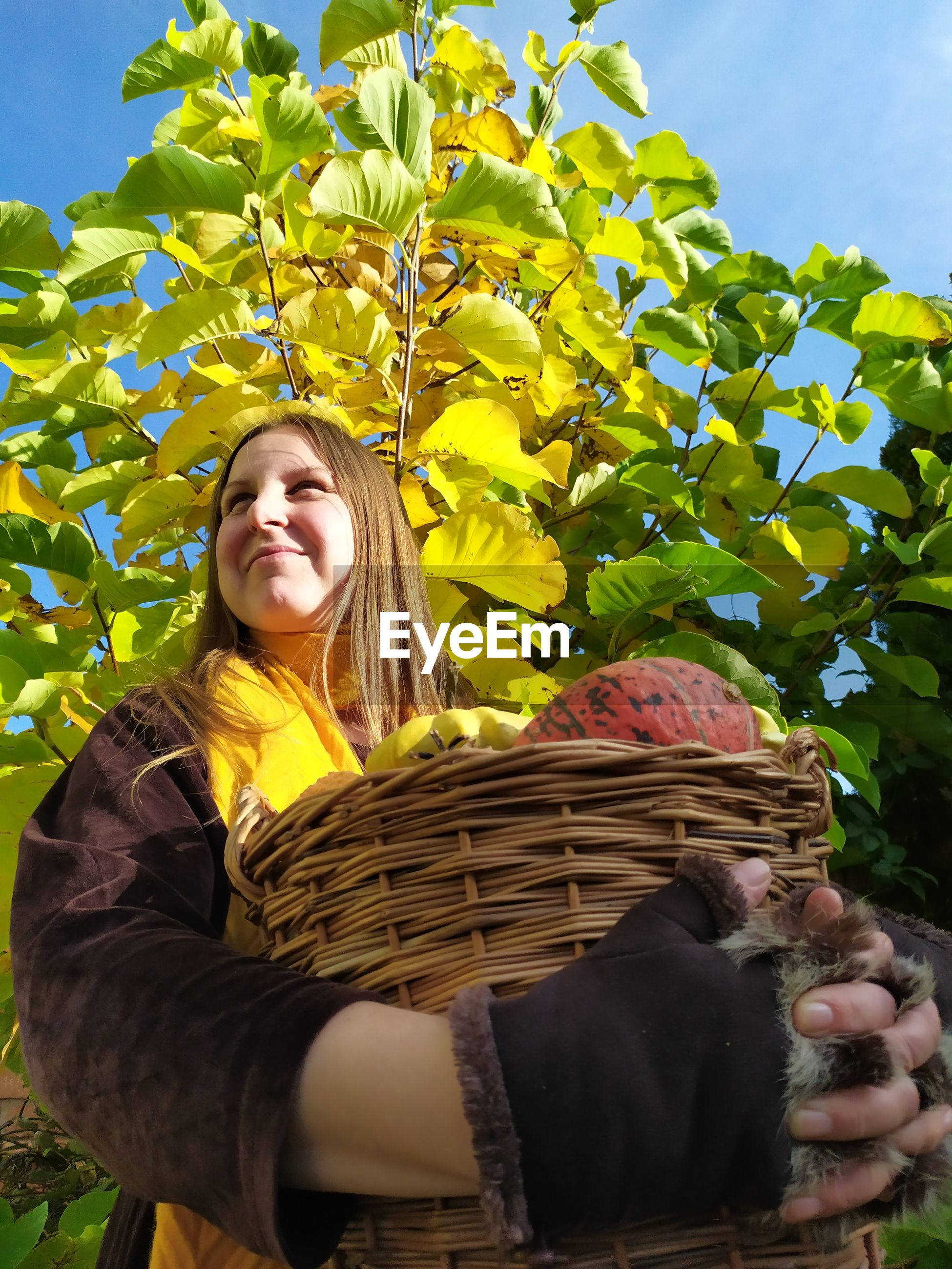Mature woman holding basket with pumpkins standing against plants and blue sky