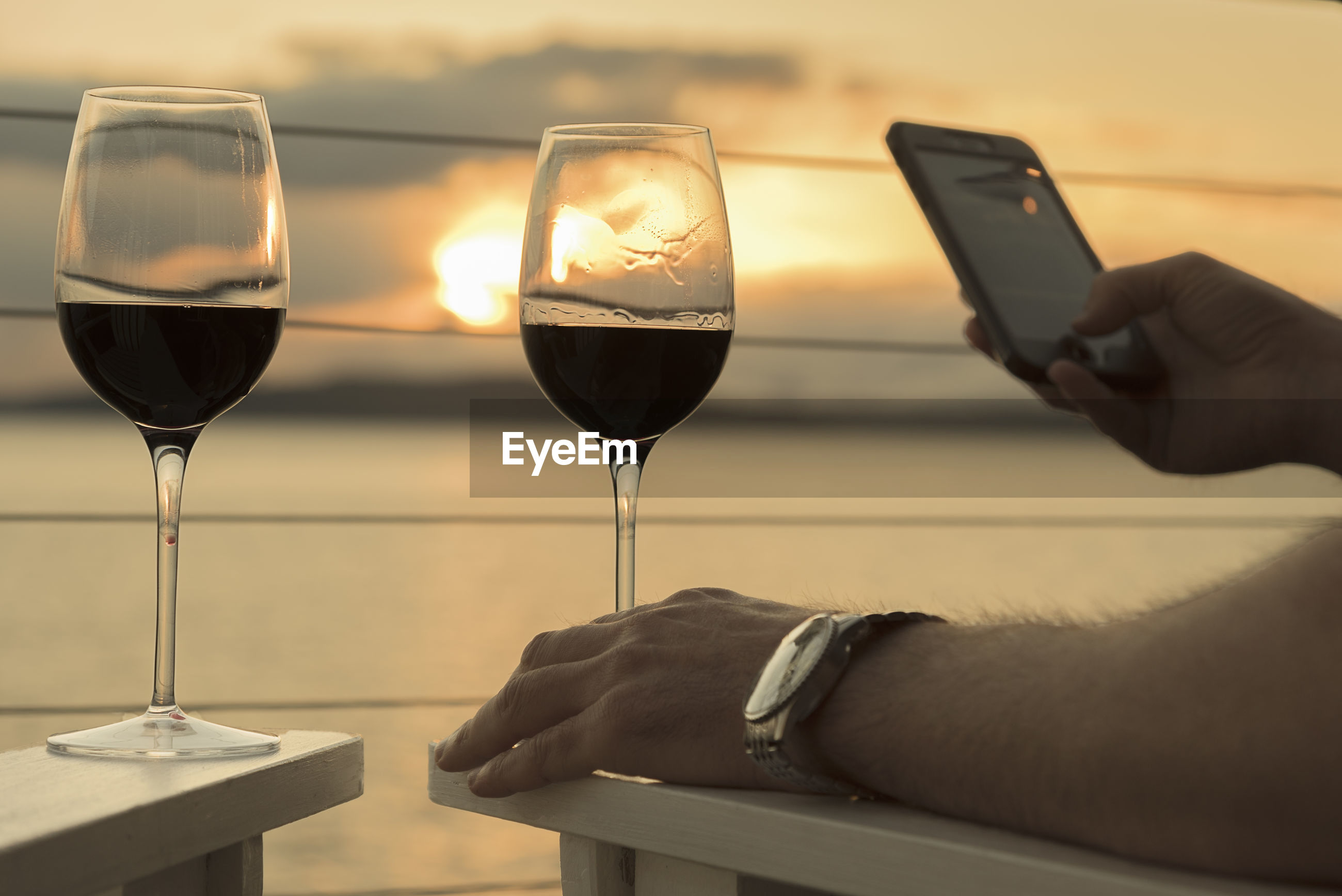 Cropped hands of man with wine glasses using phone by sea against sky during sunset