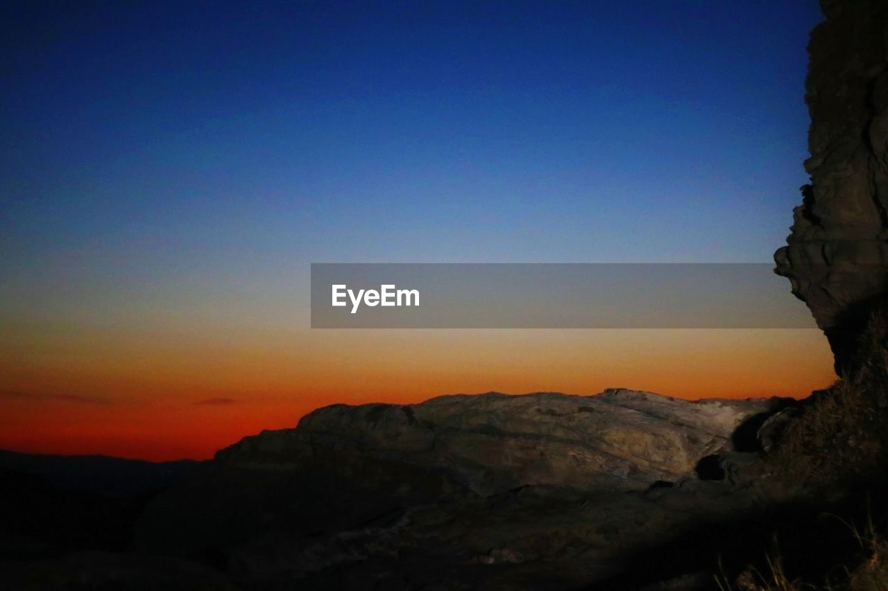mountain, sunset, rock - object, beauty in nature, rock formation, tranquil scene, nature, copy space, scenics, tranquility, no people, clear sky, outdoors, blue, sky, physical geography, day