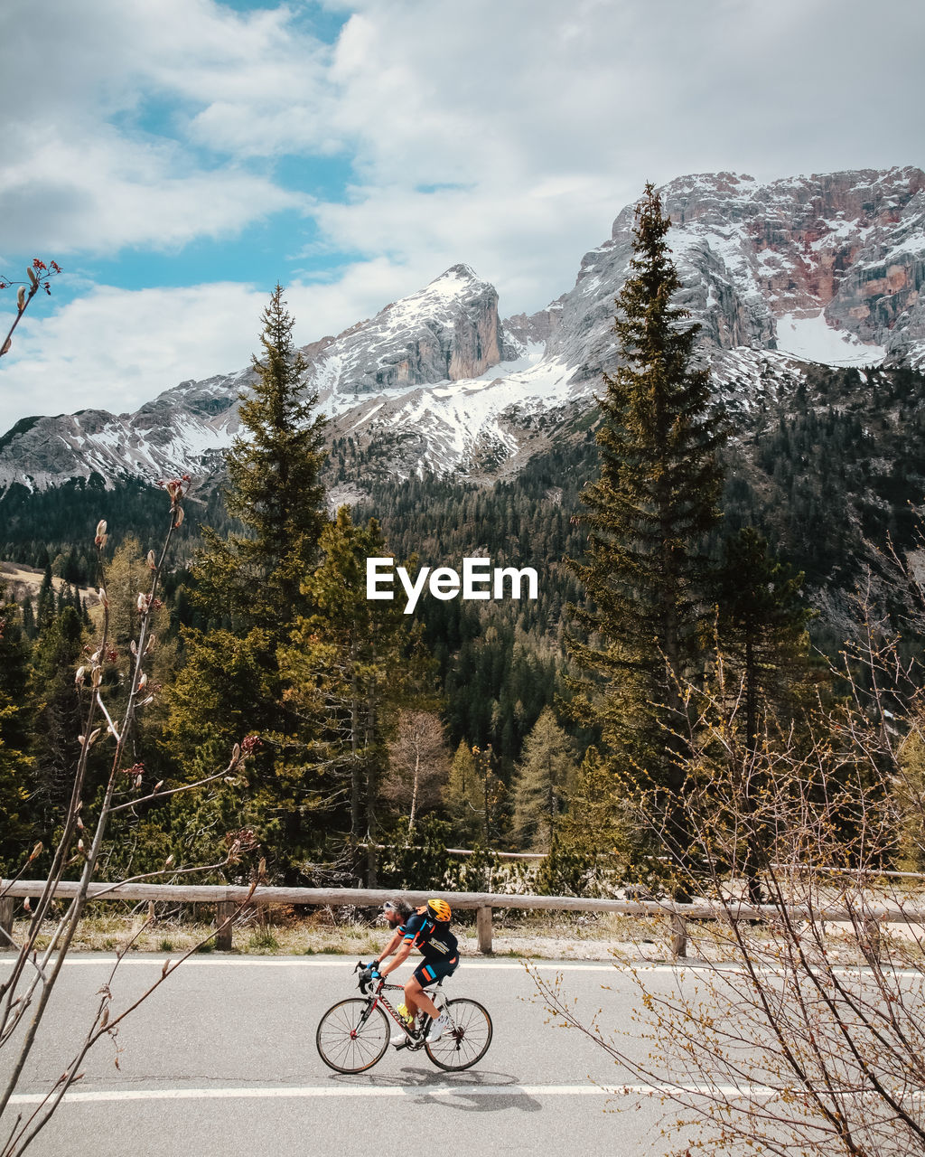 MAN CYCLING ON SNOW COVERED MOUNTAINS