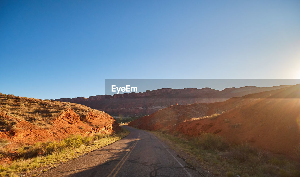 sky, road, the way forward, direction, transportation, mountain, nature, clear sky, copy space, beauty in nature, sunlight, tranquility, non-urban scene, tranquil scene, environment, scenics - nature, landscape, day, blue, no people, diminishing perspective, outdoors