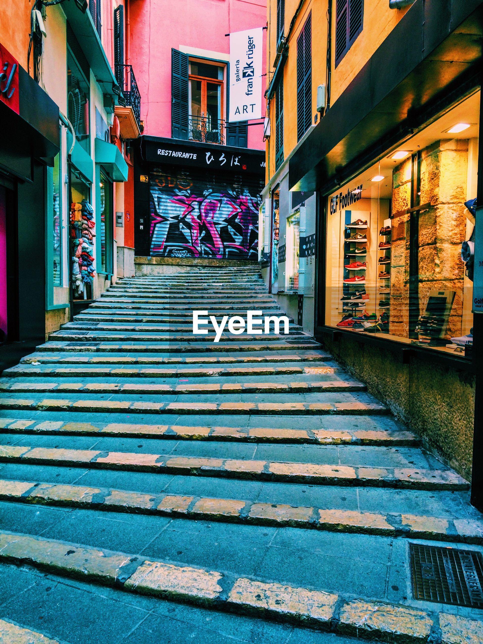 Walkway amidst stores in city
