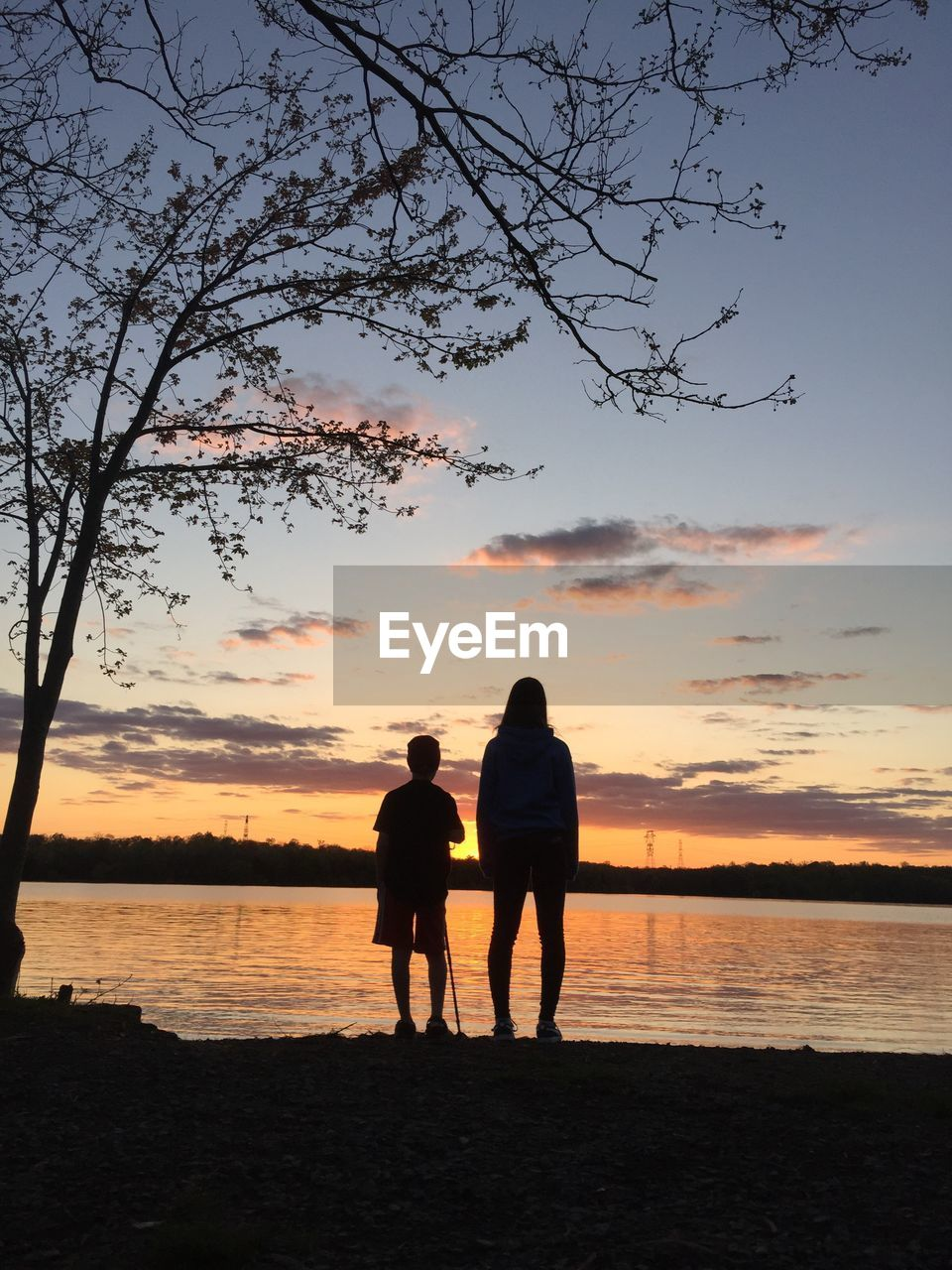 Rear View Of Boy And Girl Standing By Riverbank Against Sky During Sunset