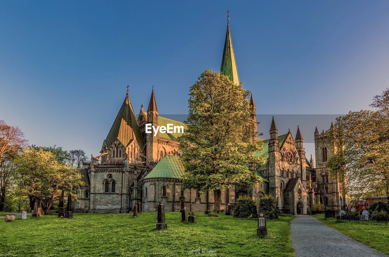 architecture, religion, place of worship, built structure, spirituality, building exterior, history, day, outdoors, travel destinations, ancient, no people, grass, clear sky, sky, nature, tree, ancient civilization