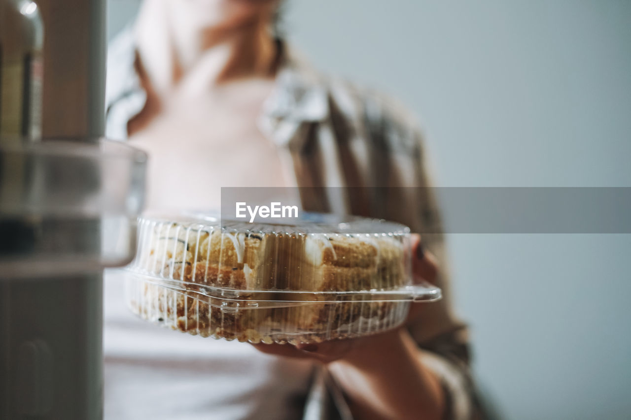 Attractive friendly brunette woman middle age in cozy cardigan eating cake