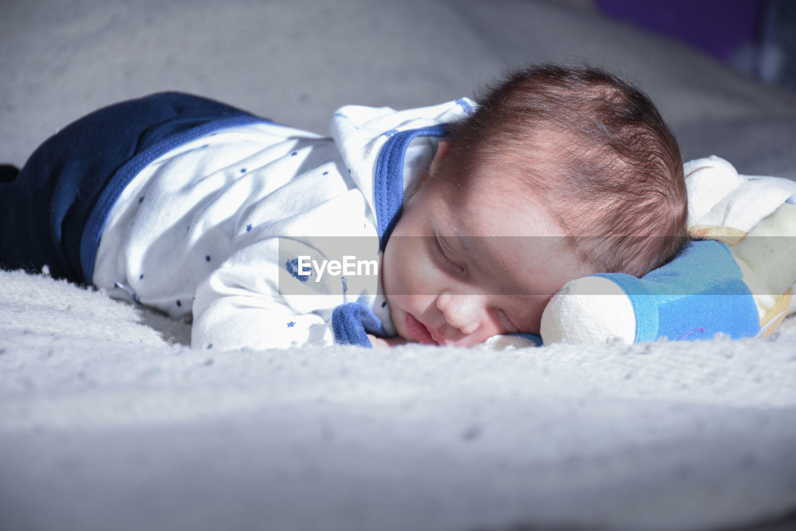 Close-up of cute baby boy sleeping on bed