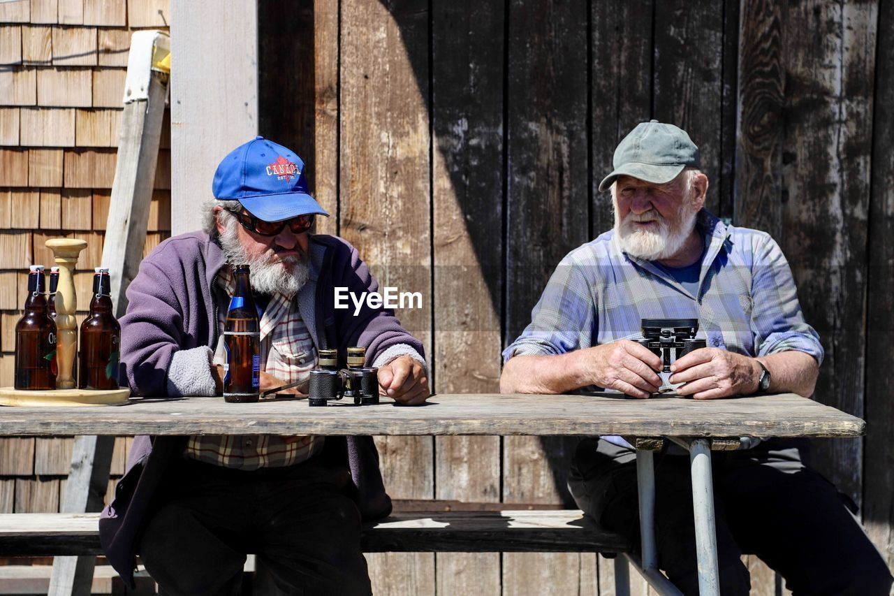 real people, wood - material, front view, leisure activity, men, sitting, lifestyles, two people, males, adult, drink, people, mature men, holding, three quarter length, day, refreshment, relaxation, mature adult, outdoors