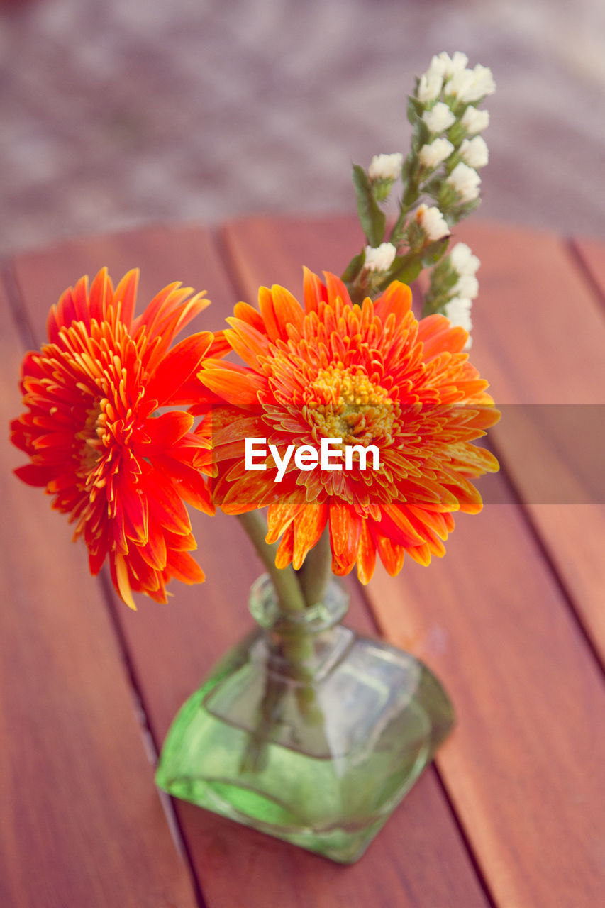 flowering plant, flower, freshness, beauty in nature, plant, flower head, close-up, petal, table, fragility, orange color, vulnerability, no people, wood - material, nature, indoors, inflorescence, focus on foreground, vase, high angle view, flower arrangement, bouquet, bunch of flowers
