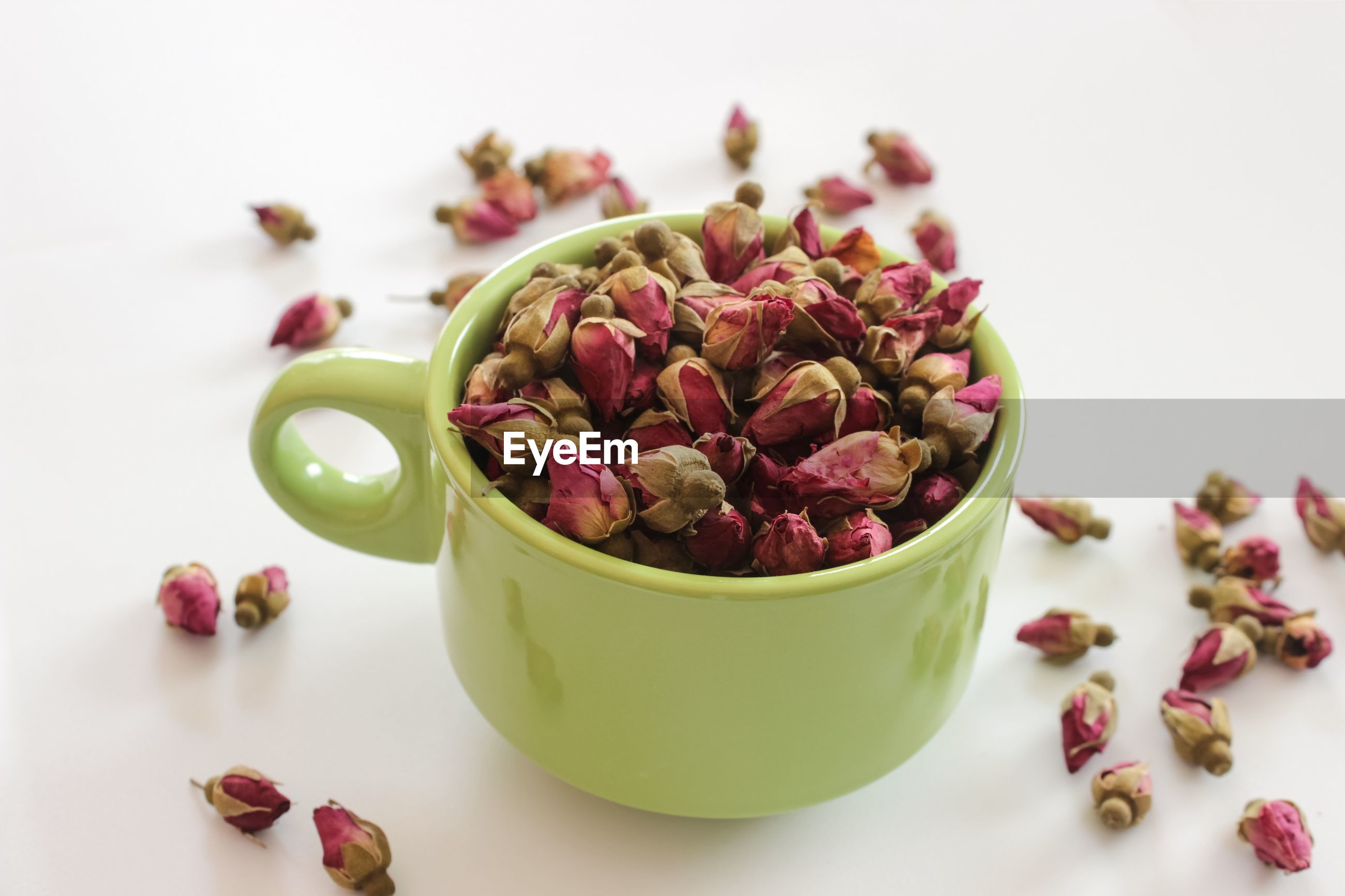 High angle view of dry rose buds in tea cup against white background