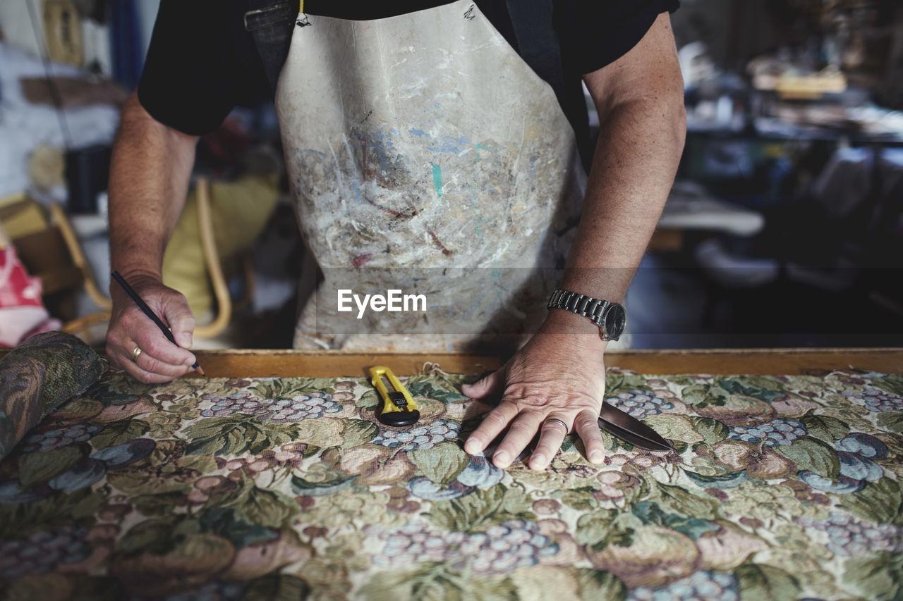 Midsection of artist making design on textile at workshop