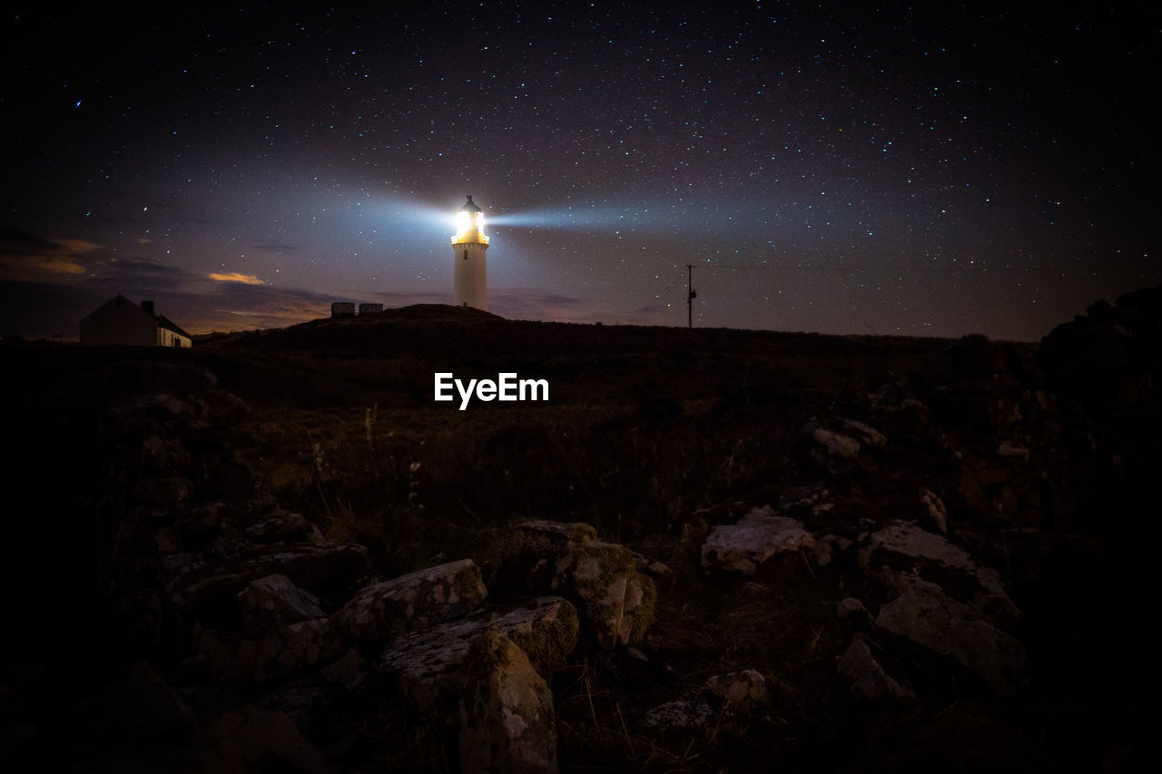 Scenic View Of Lighthouse On Hill Against Sky At Night