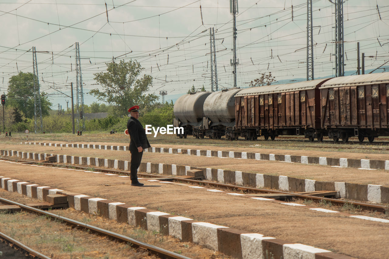 MAN STANDING ON RAILROAD TRACK AGAINST TRAIN