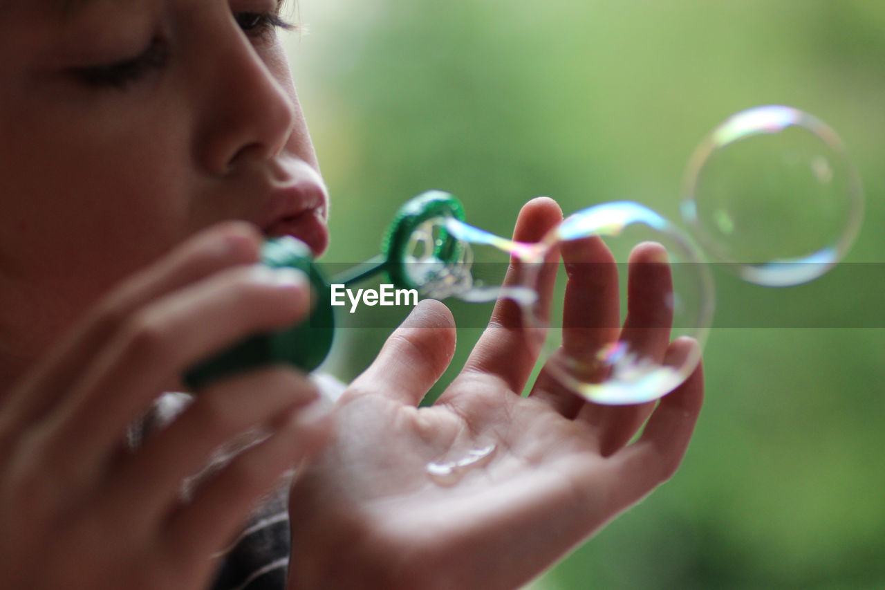 Close-Up Of Boy Blowing Bubbles