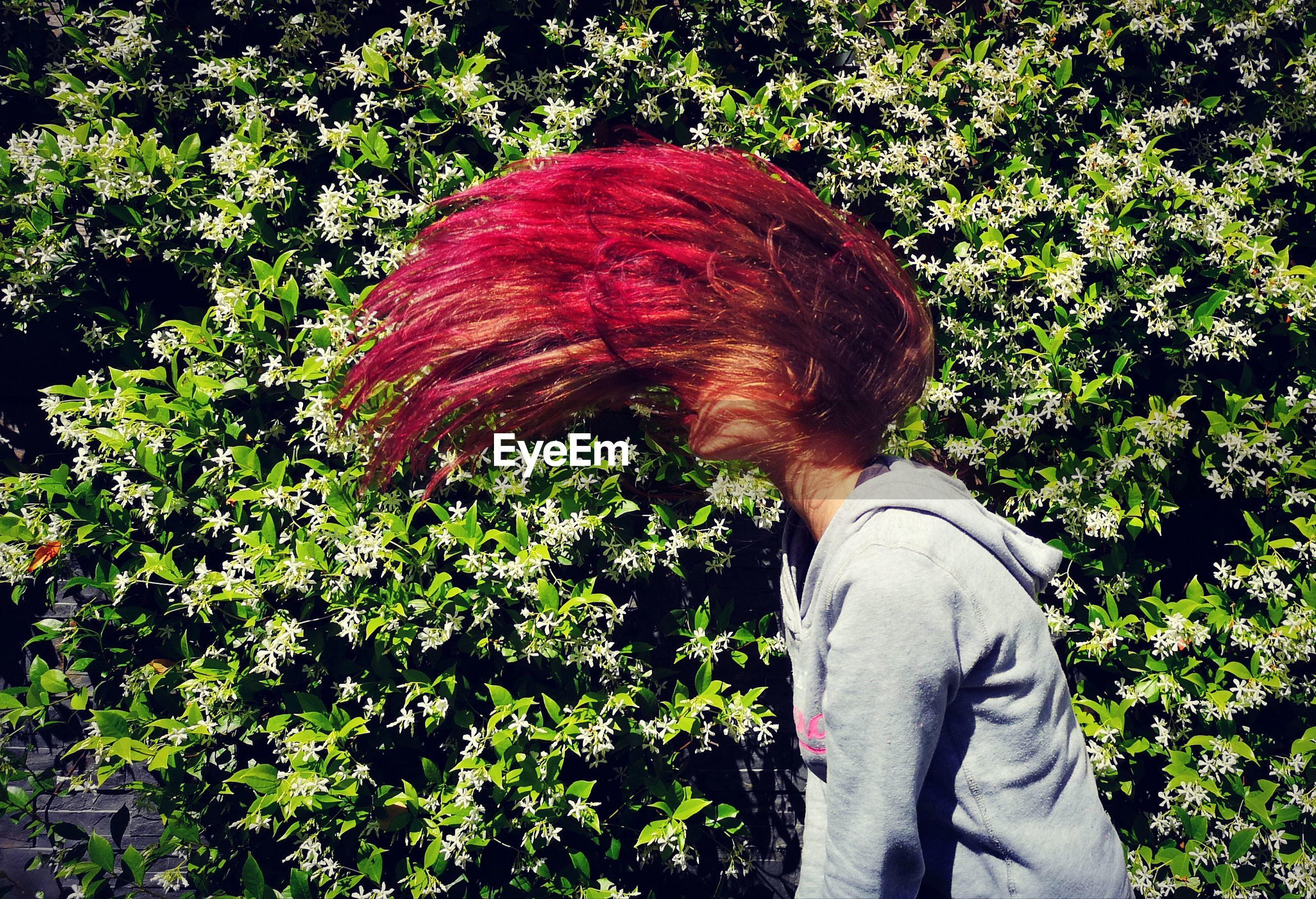 Side view of teenage girl tossing hair while standing against plants