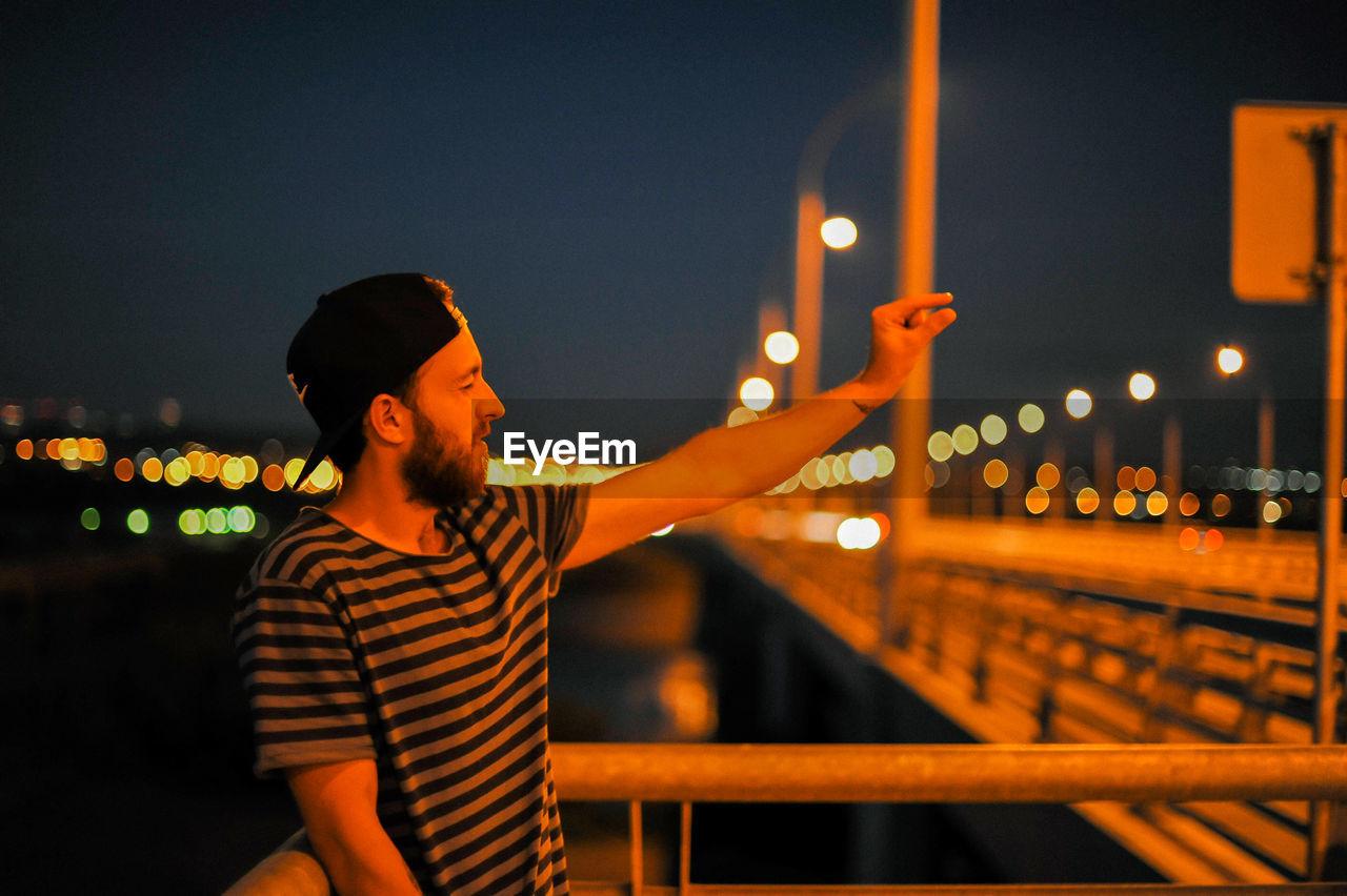 Young man gesturing on bridge at night