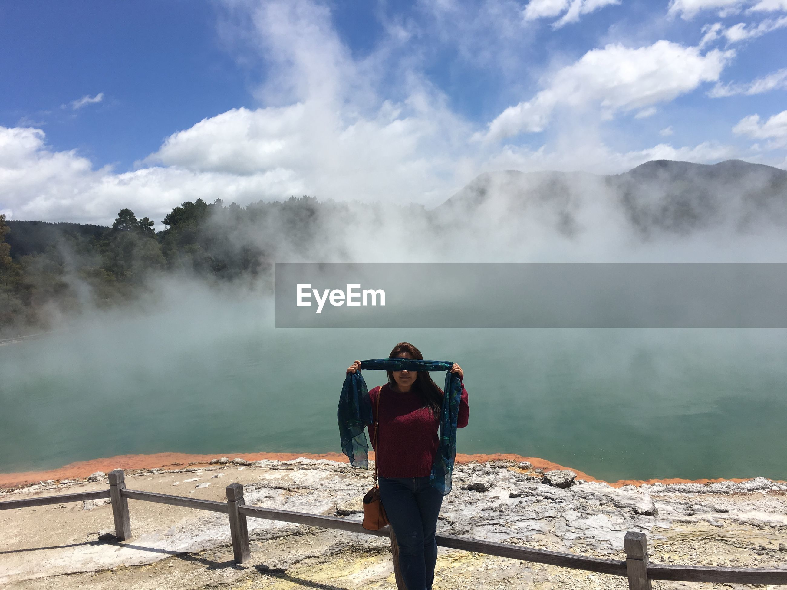 Woman covering eyes with scarf on mountain by lake against sky
