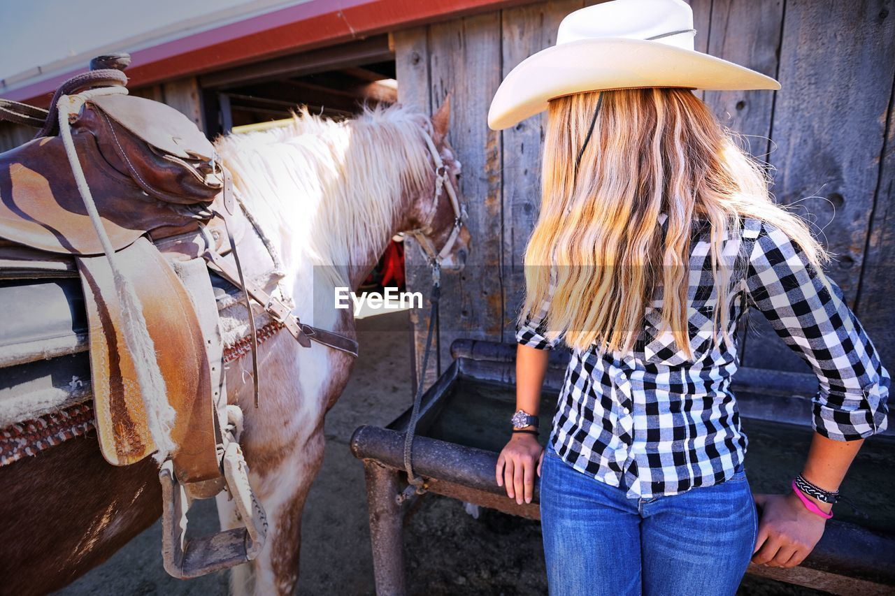 livestock, real people, domestic animals, rear view, lifestyles, standing, outdoors, one animal, day, one person, women, occupation, blond hair, mammal, adult, people