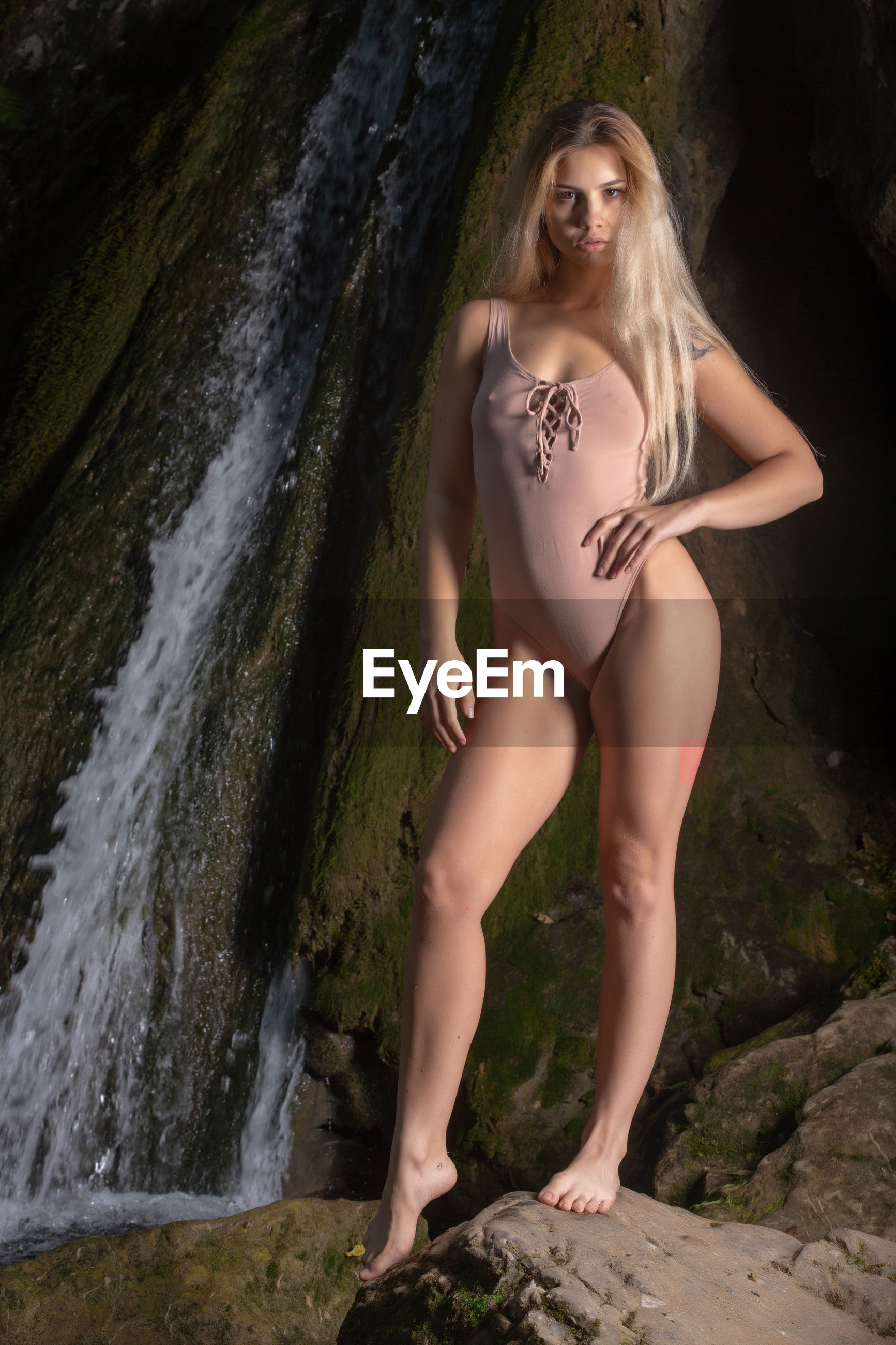 Full length portrait of woman standing on rock against waterfall
