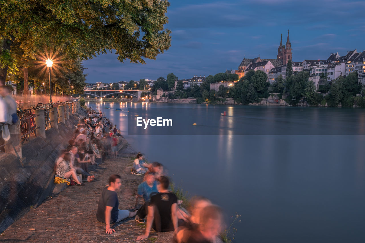 GROUP OF PEOPLE BY RIVER IN CITY