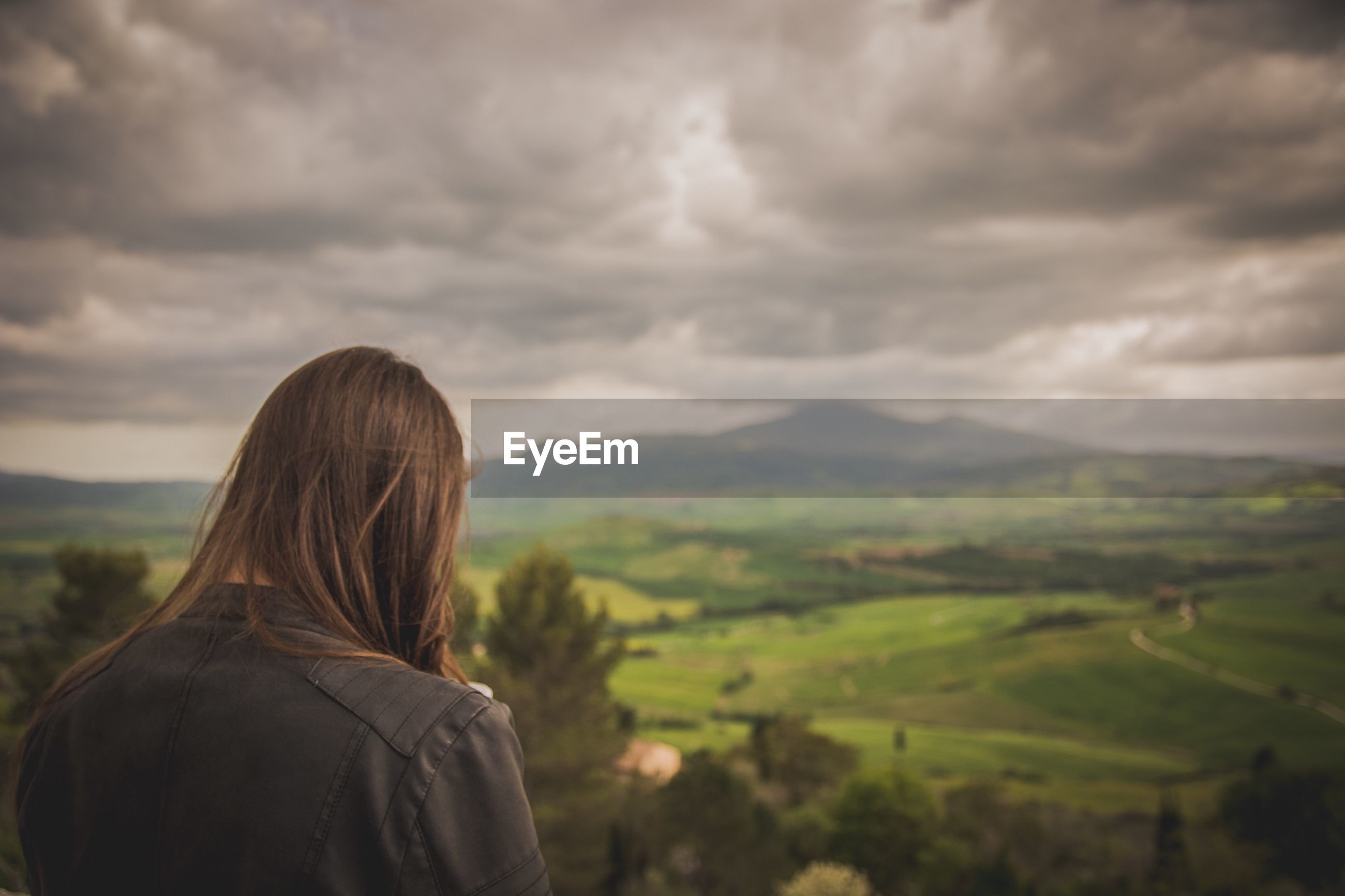 Woman looking at mountains against cloudy sky