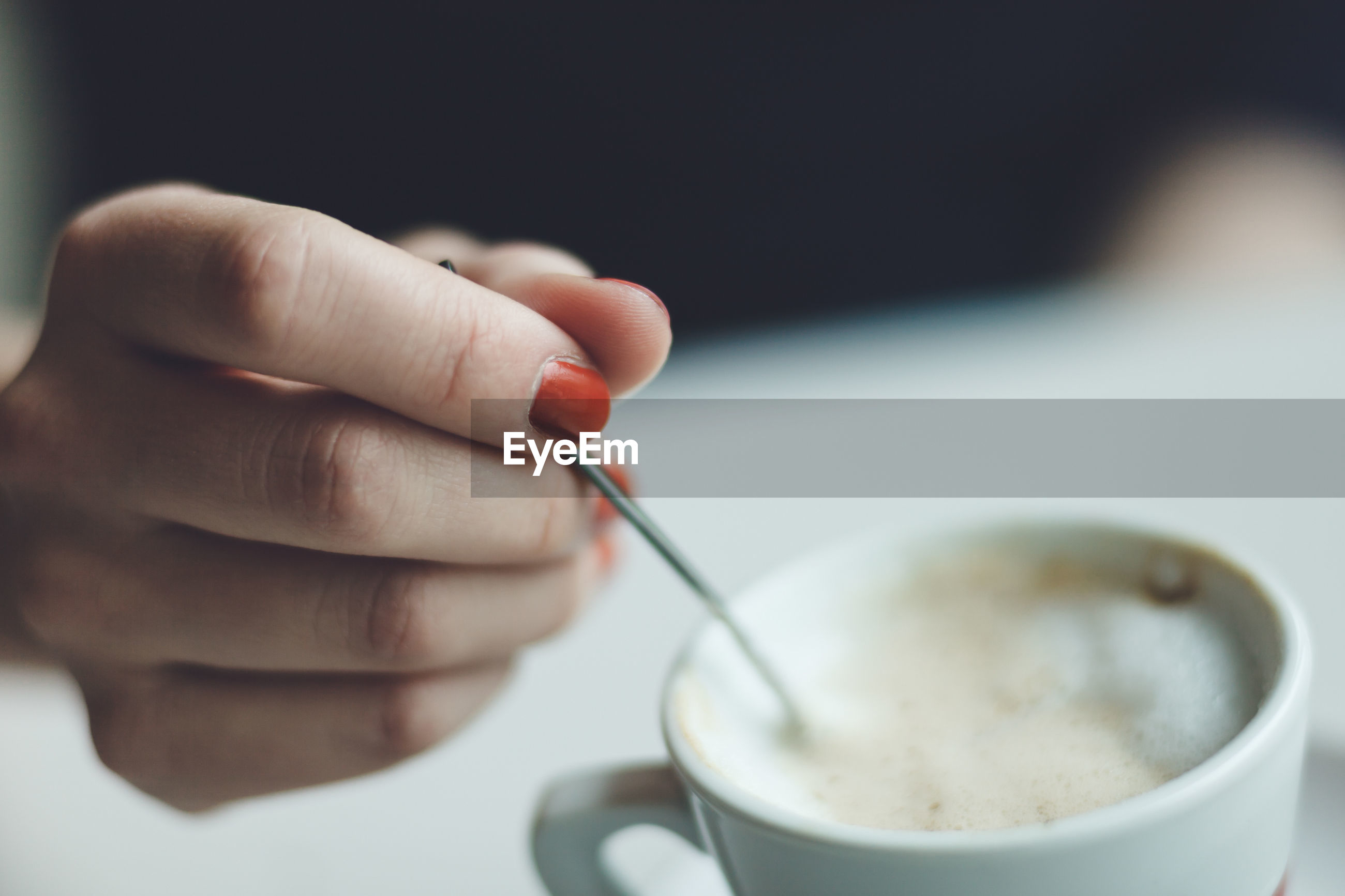 Close-up of hand holding coffee cup and spoon