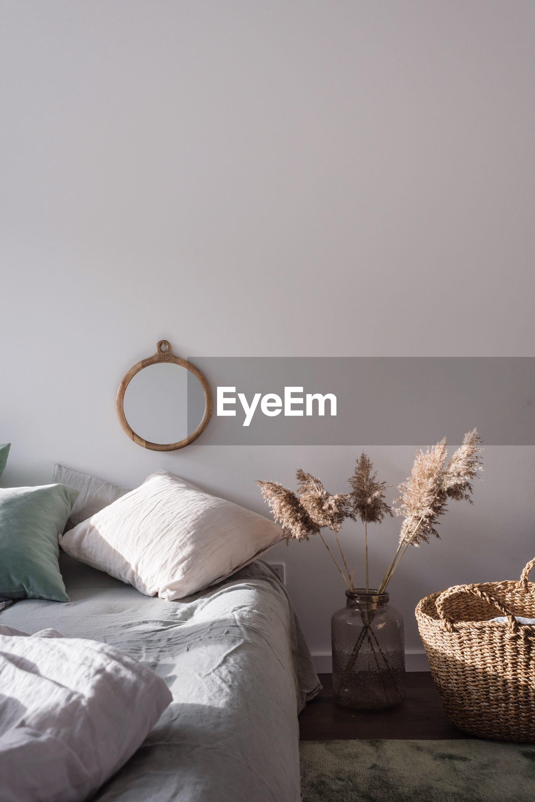 Wicker basket by plant in bedroom