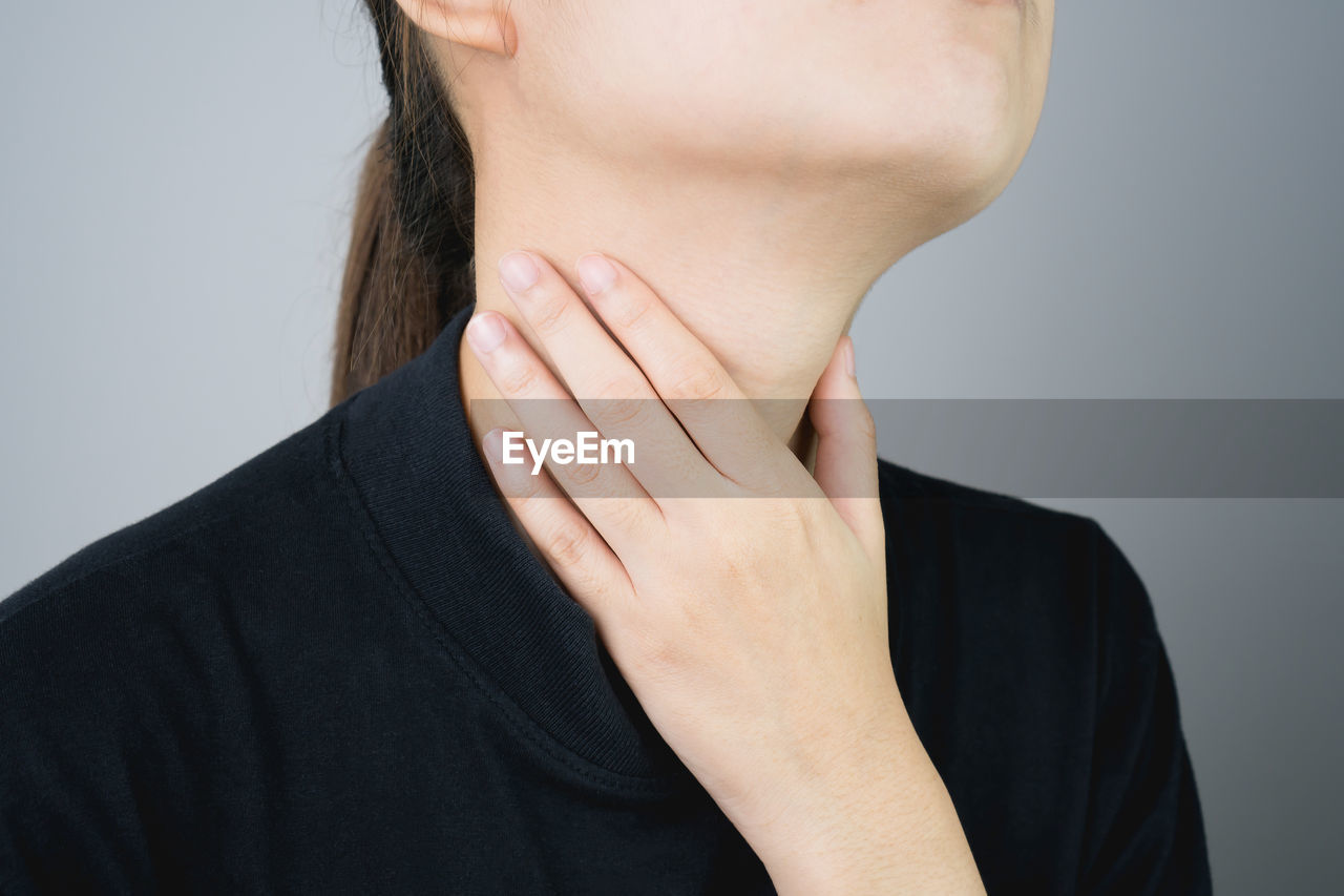 Midsection Of Woman Suffering From Neckache Against Gray Background