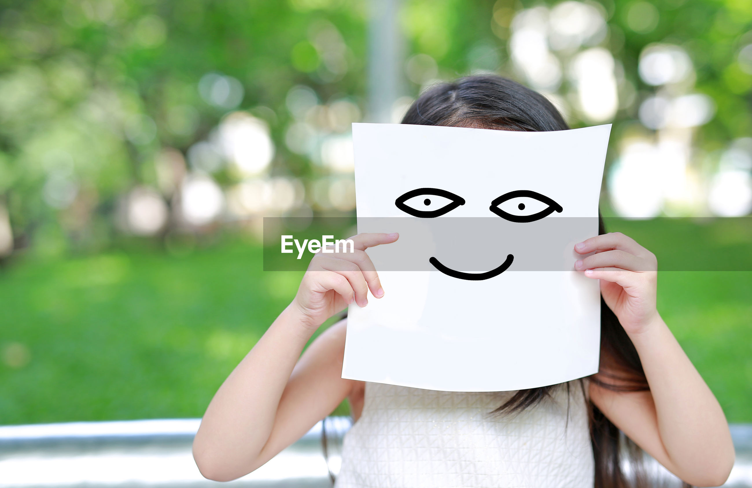 Playful girl holding paper with anthropomorphic smiley face in park