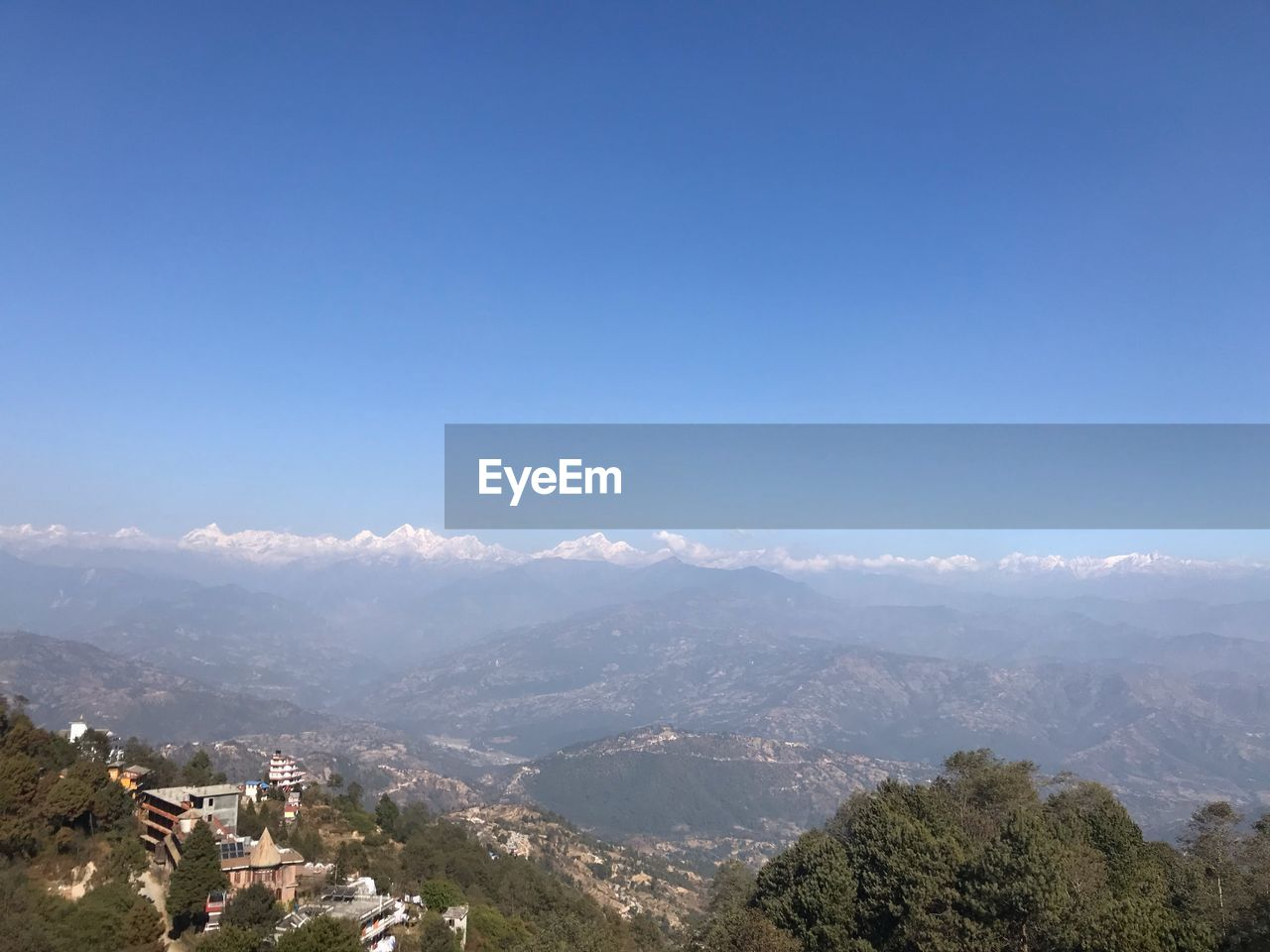 mountain, sky, scenics - nature, beauty in nature, building exterior, nature, copy space, tranquil scene, tree, day, tranquility, mountain range, architecture, plant, environment, blue, built structure, no people, landscape, outdoors, townscape