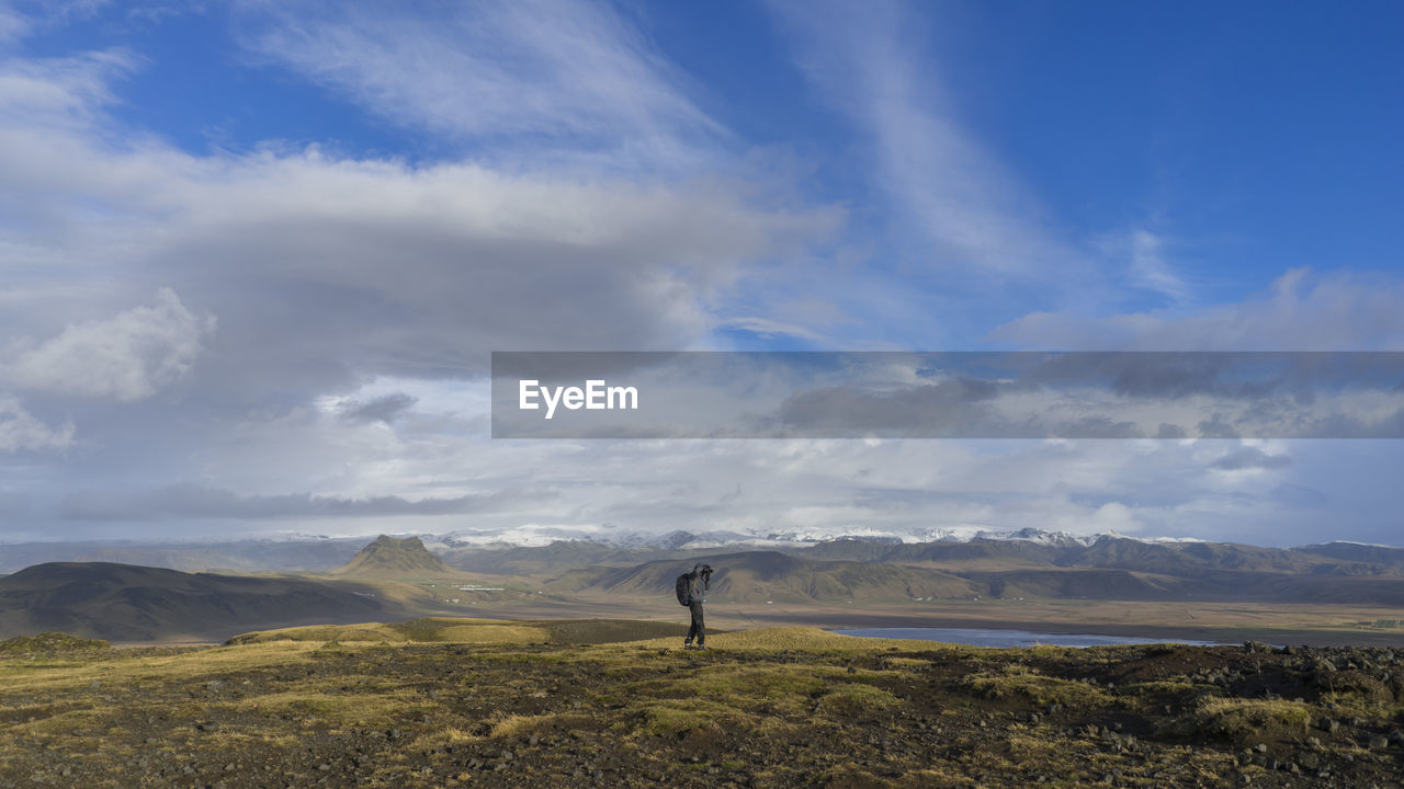 Distant Image Of Person Standing On Field Against Cloudy Sky