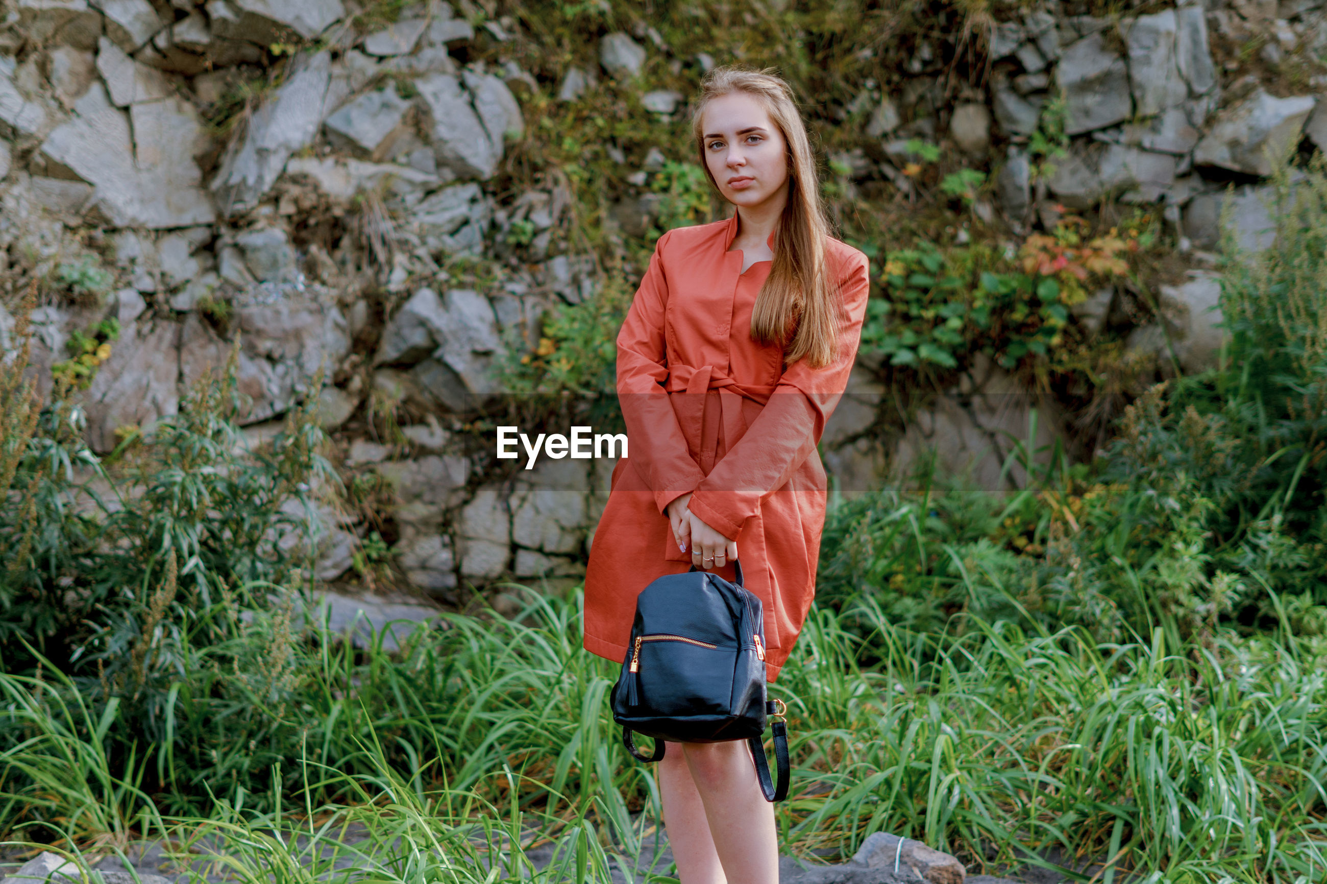 Portrait of young woman holding bag while standing on grassy field
